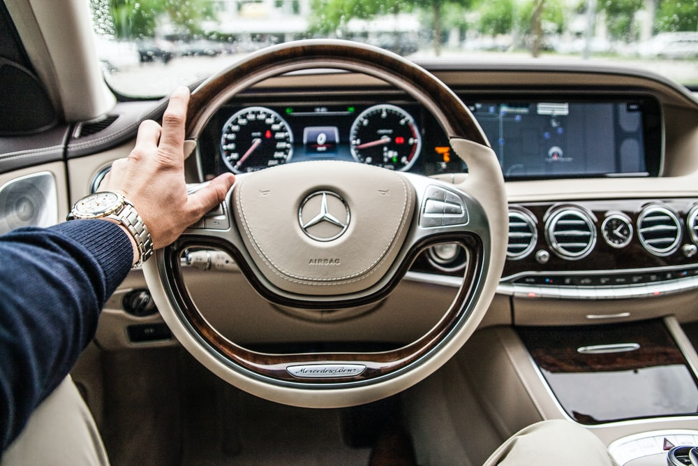 A driver with his hand on the steering wheel of a Mercedes-Benz car