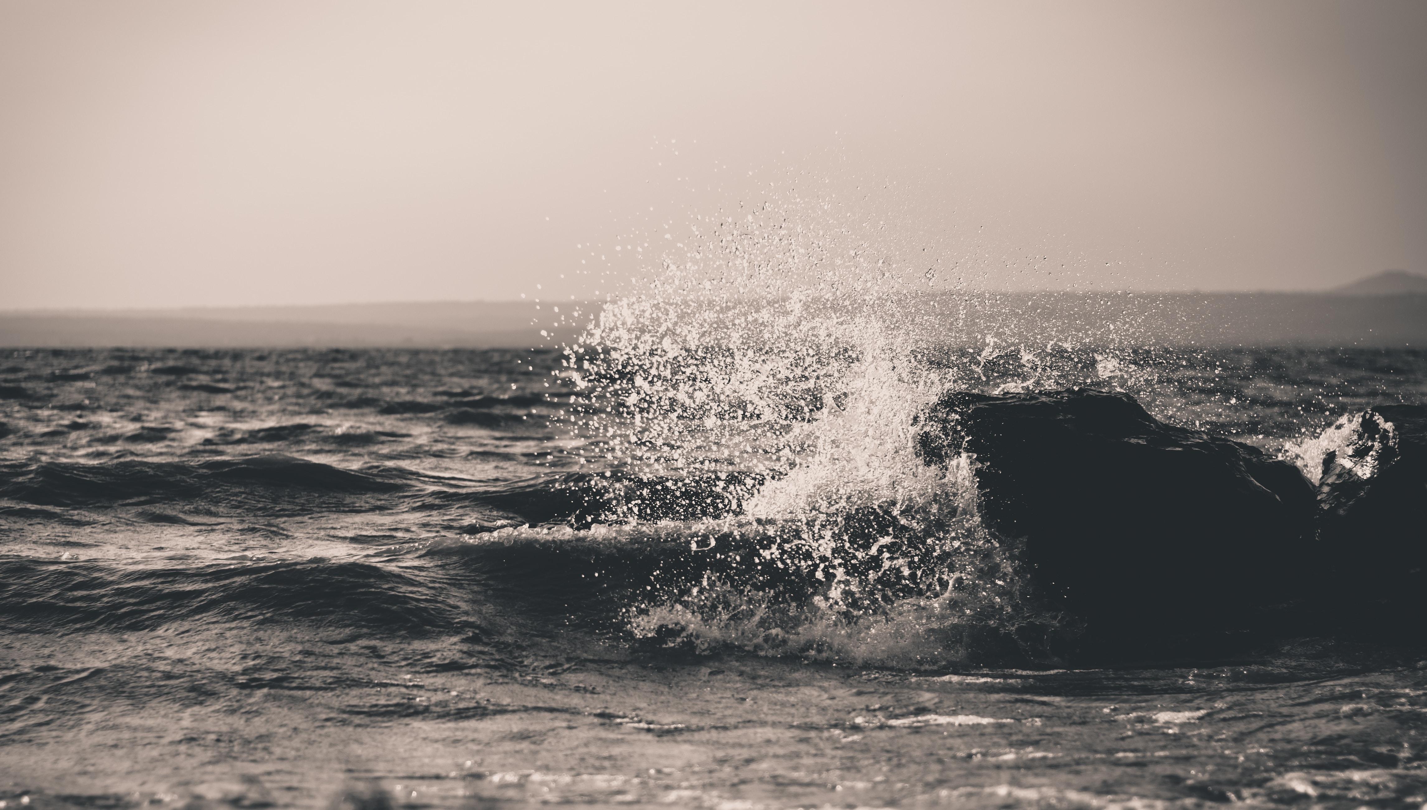 A black and white shot of water splashing over dark waves