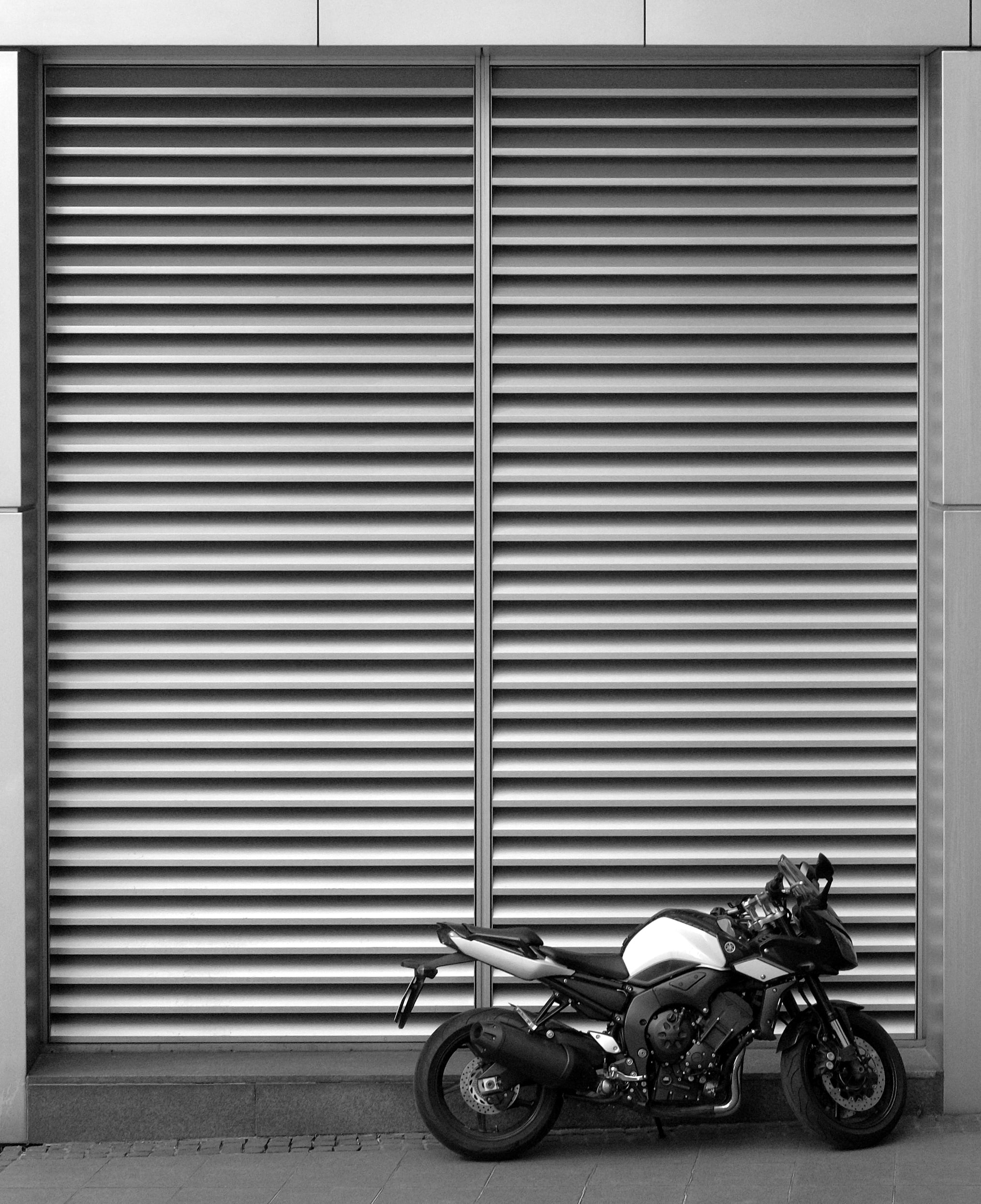 Black and white shot of motorbike parked in front of storefront shutters