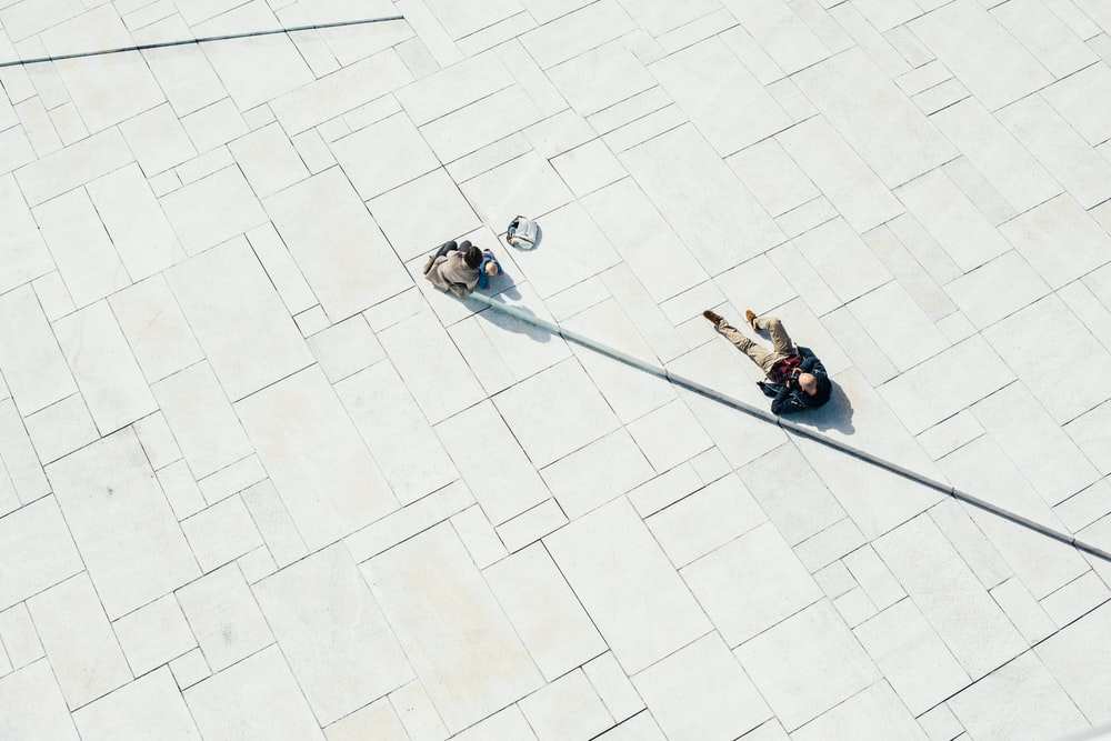 person lying on white concrete pavement during daytime