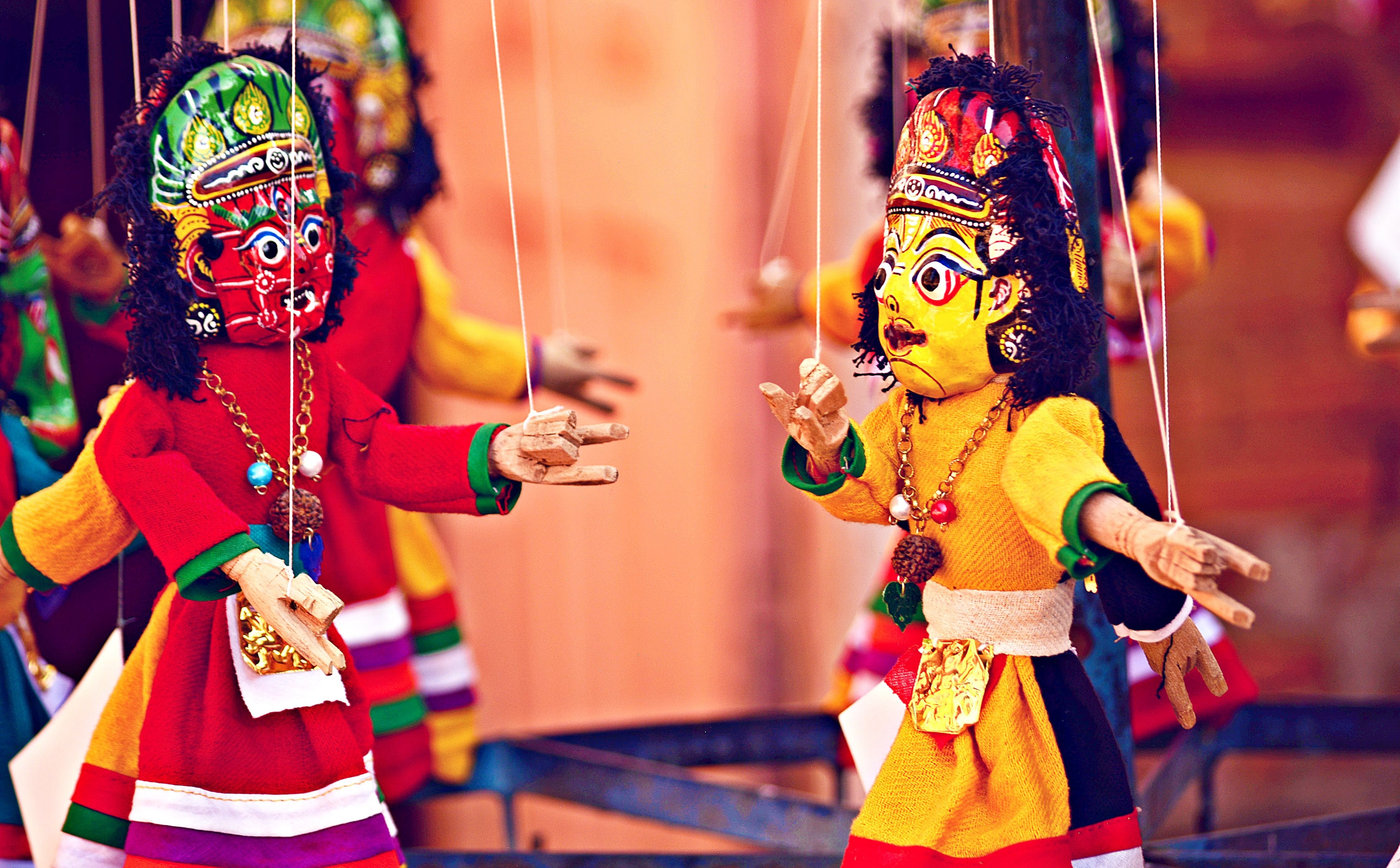 A cast of ornate puppets on strings acting out a play
