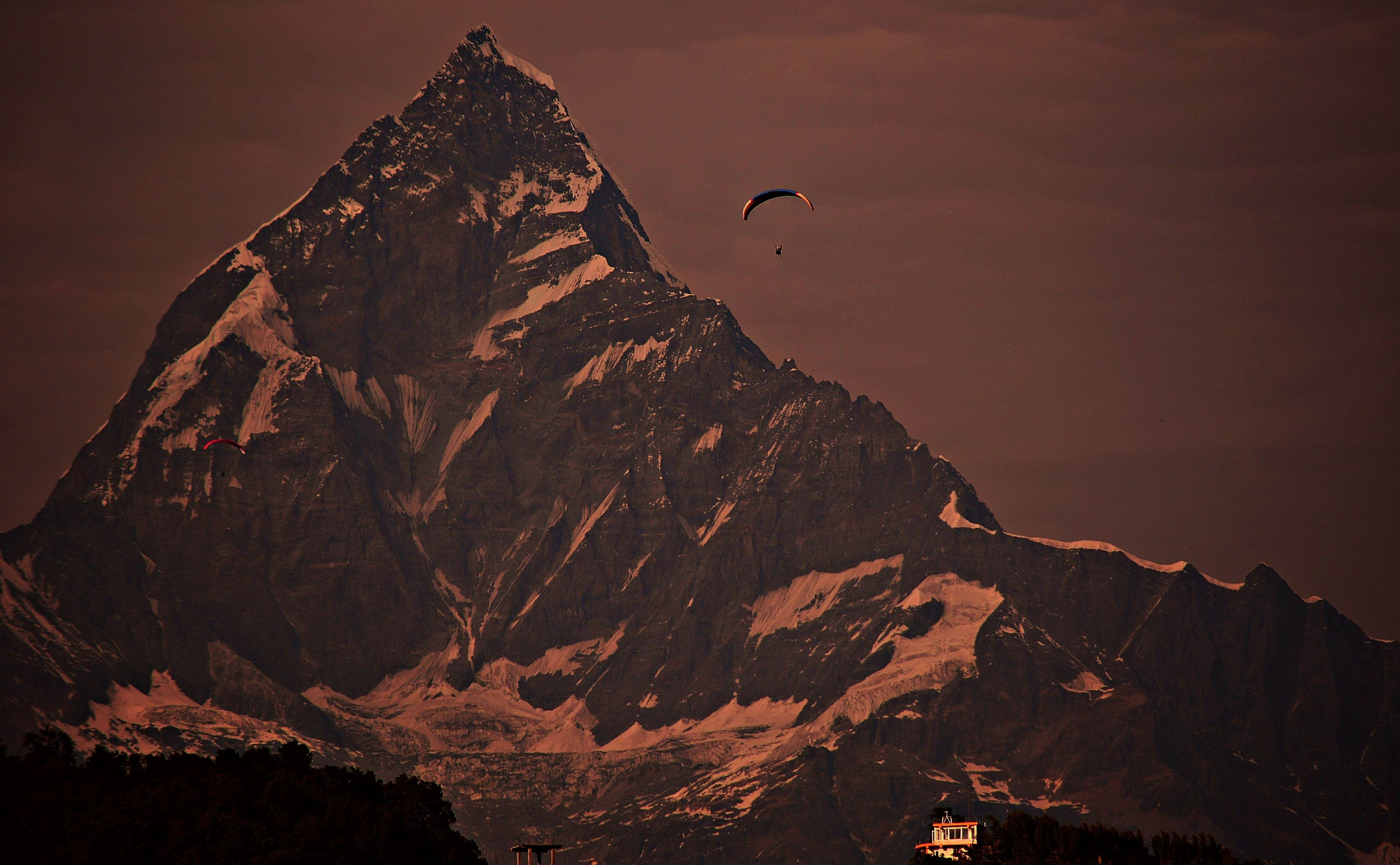 Paragliding across the icy mountain peak as an extreme sport