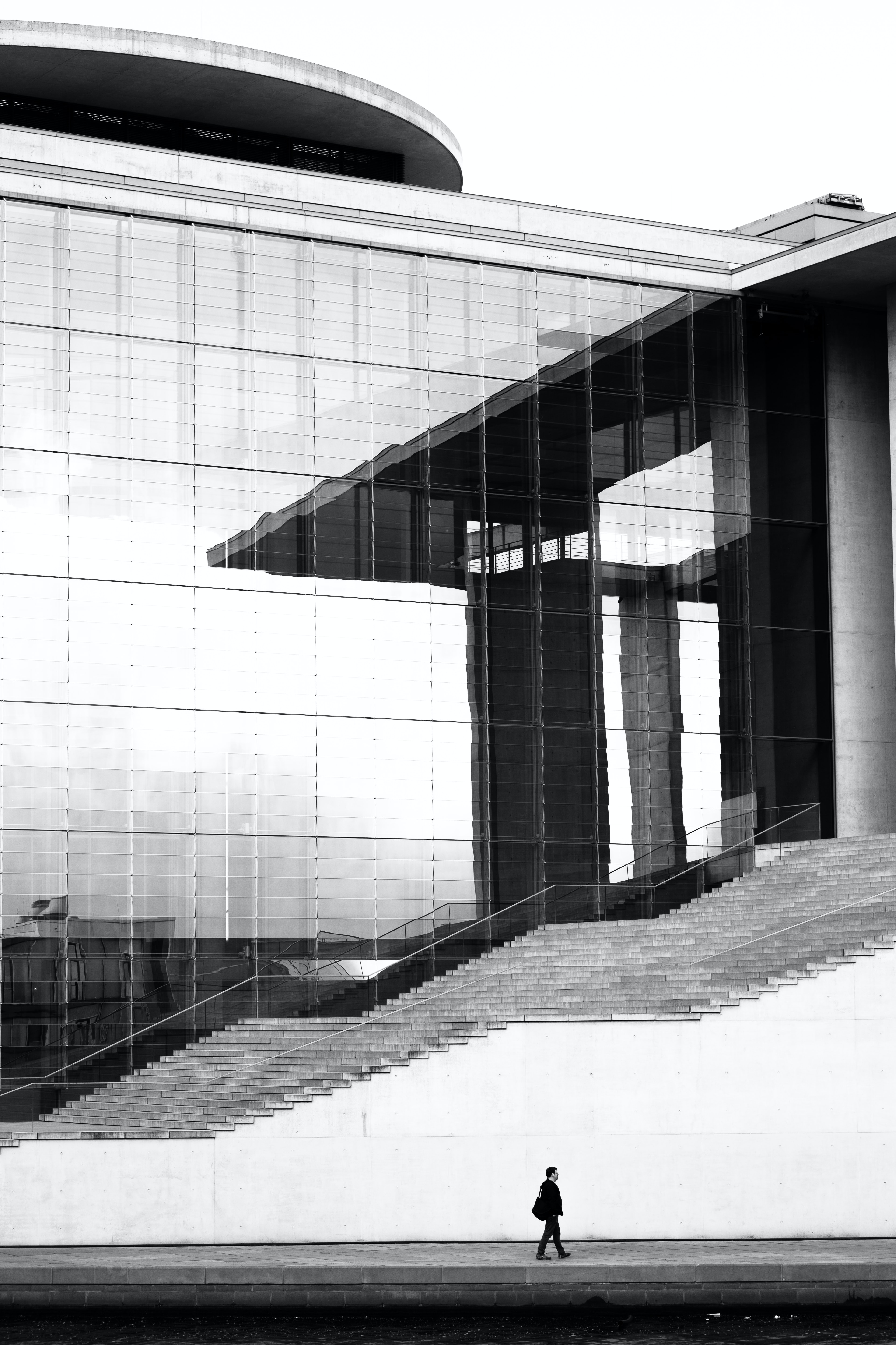 grayscale photo of man walking on concrete pavement beside high building