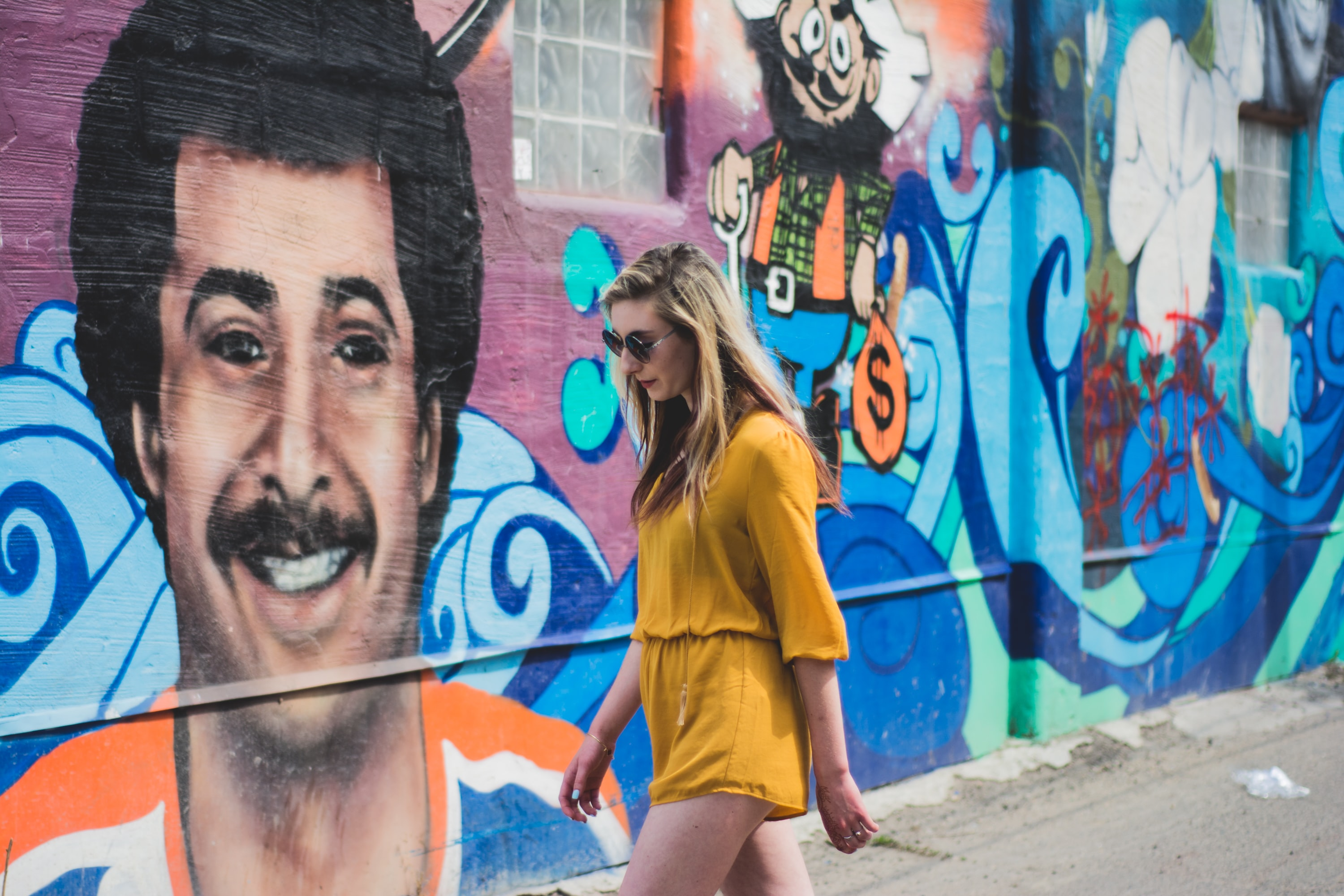 Attractive young blonde woman in sunglasses and yellow dress walking past colorful face graffiti artwork