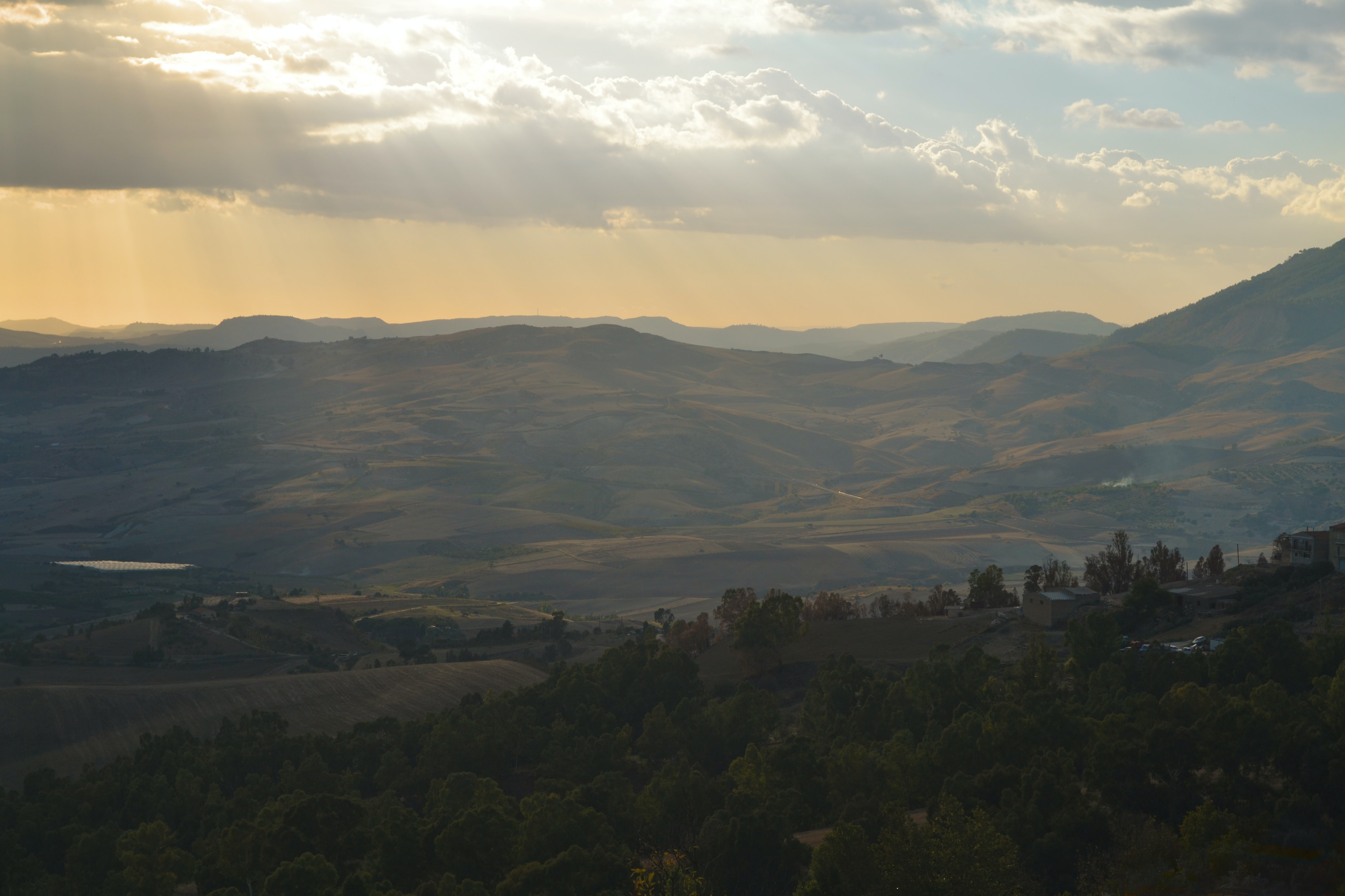 An Italian landscape of mountains and rolling hills during golden hour in Sicily