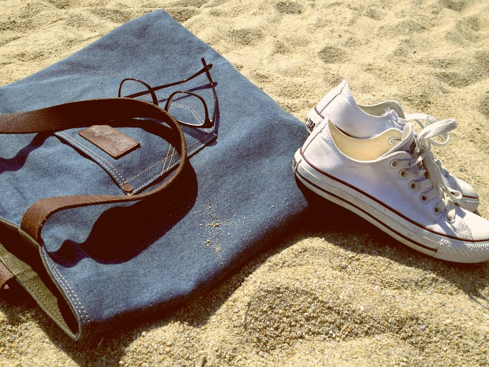 pair of white low-top sneakers on brown sand