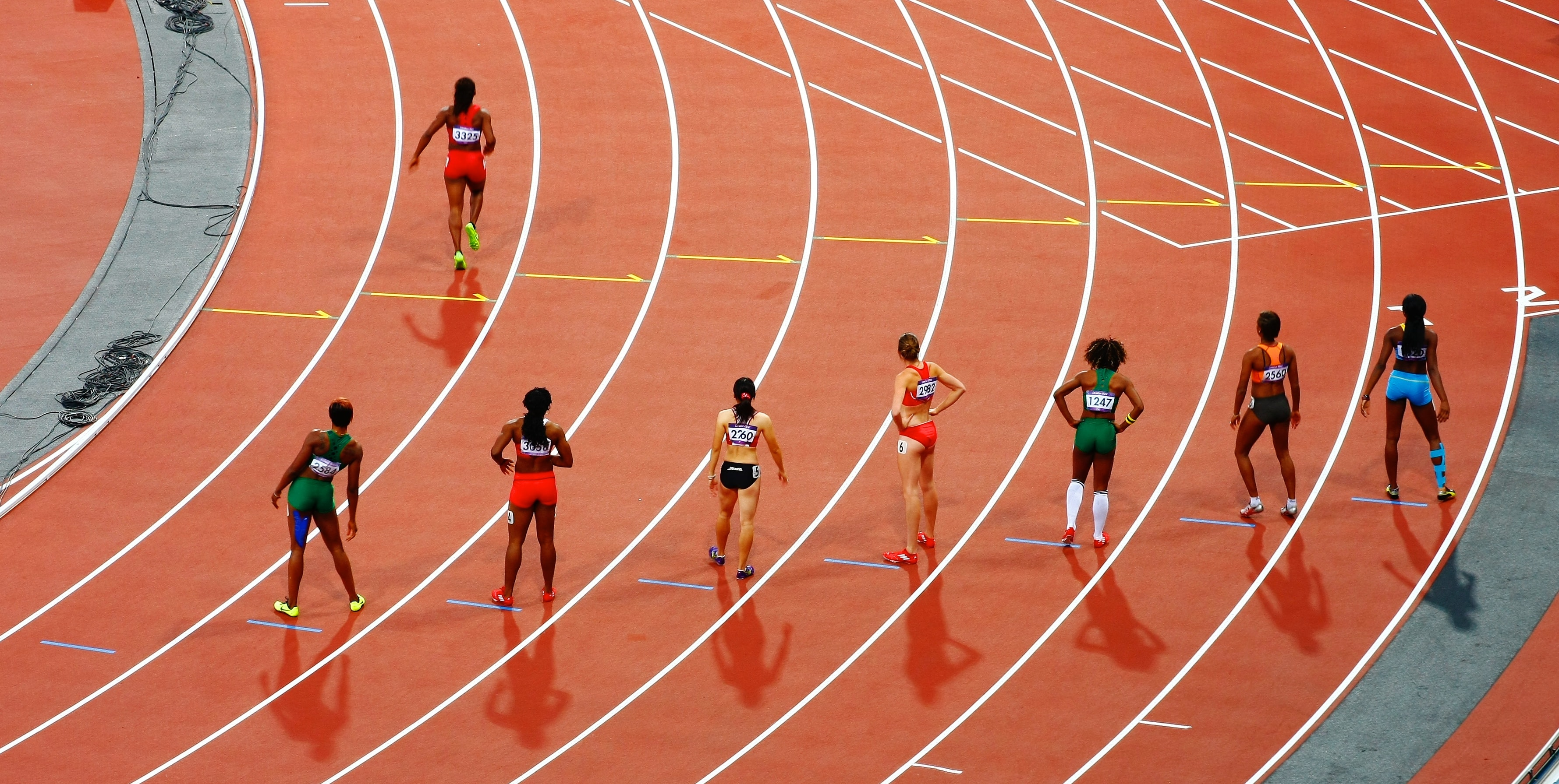 A woman running on a race track while seven others stand back and stretch