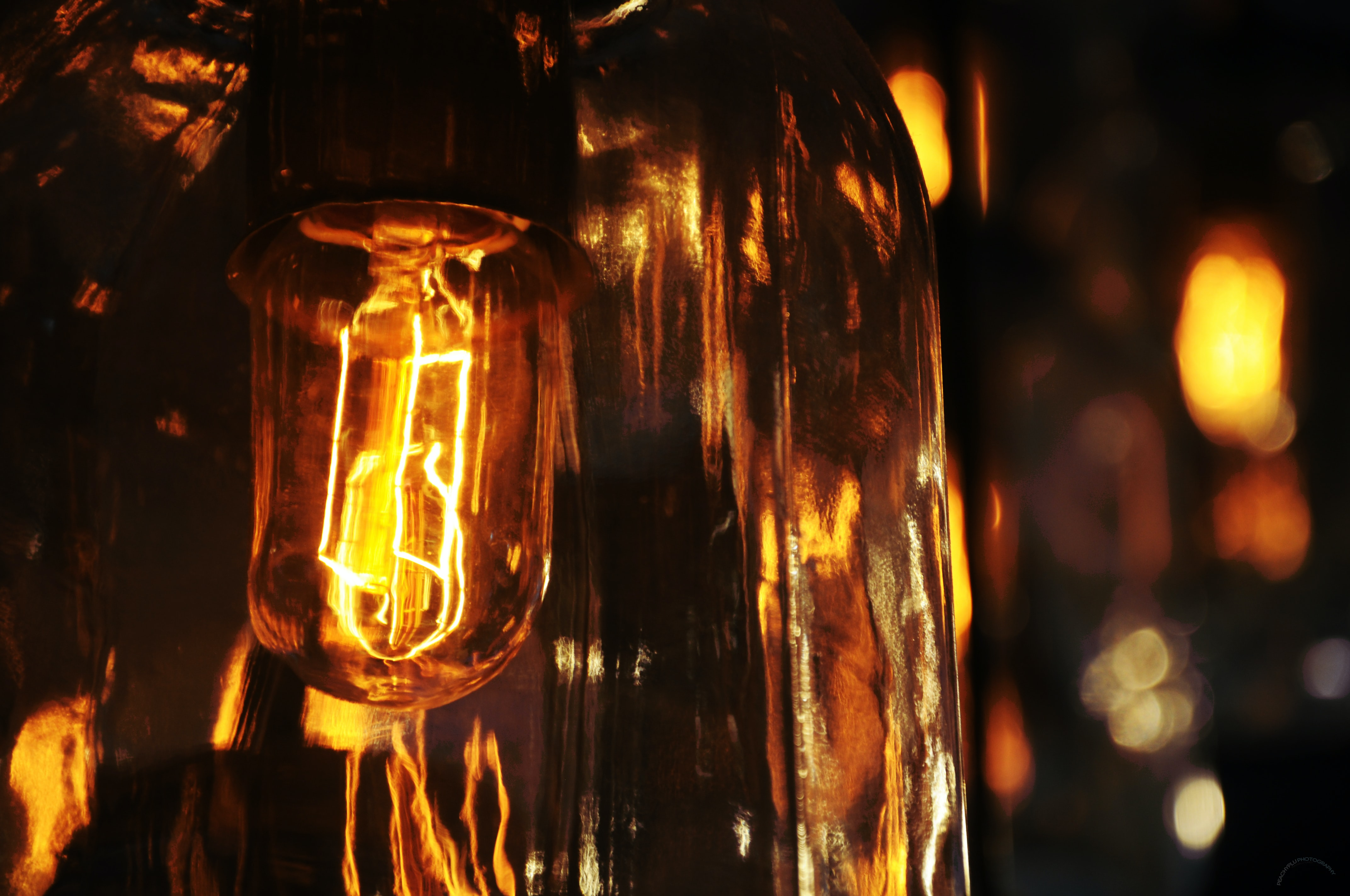 The fillaments of a lightbulb emitting a warm glow and reflecting in the glass of the bulb