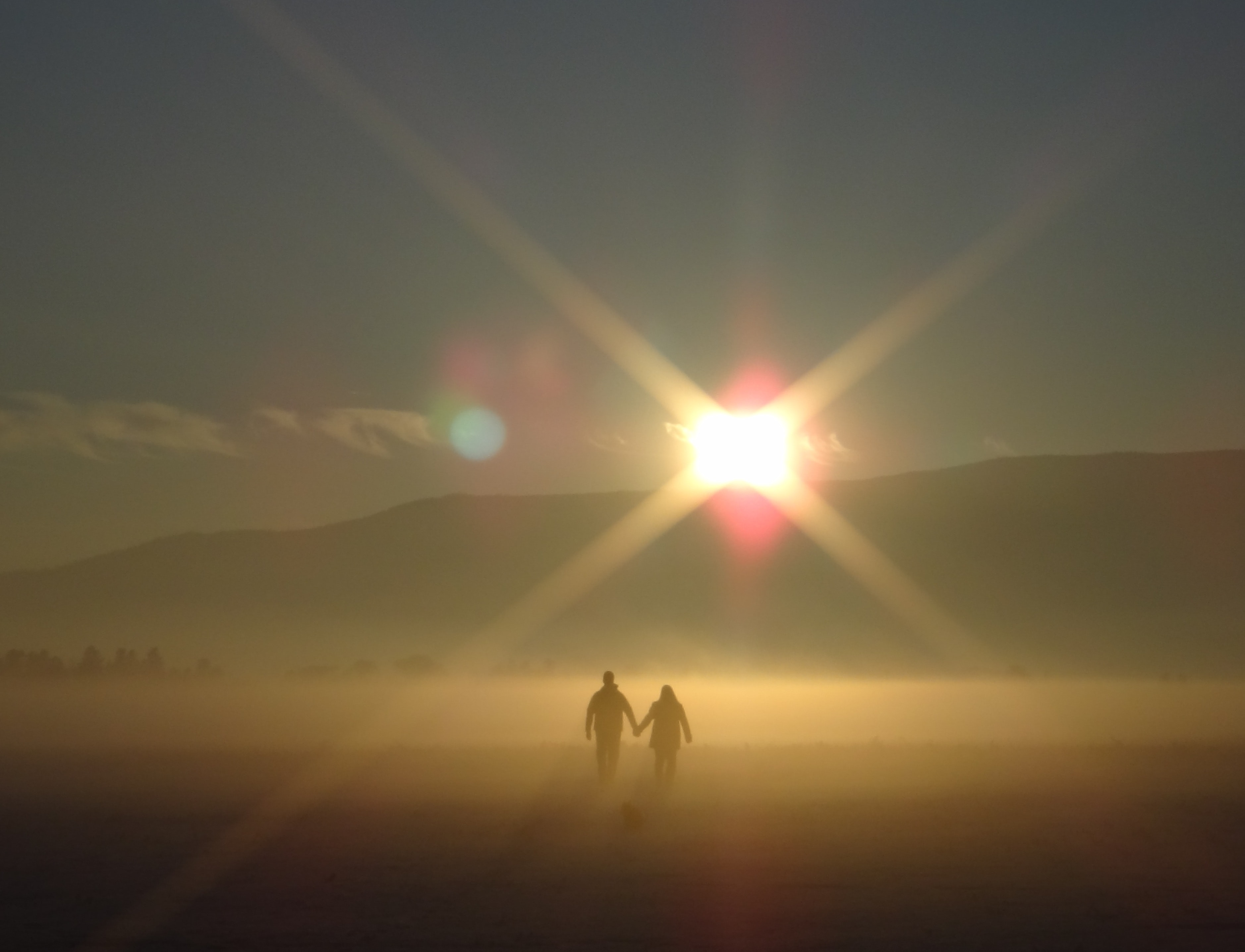 Two people walking through a foggy area during sunset