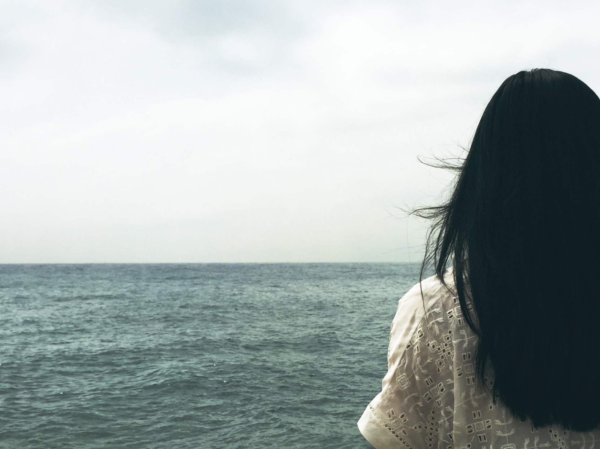 A dark-haired woman looking off into the choppy sea stretching to the horizon