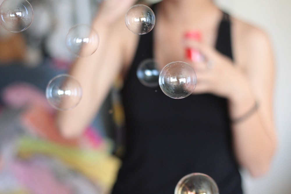 selective focus photo of bubbles blown by person wearing black tank top
