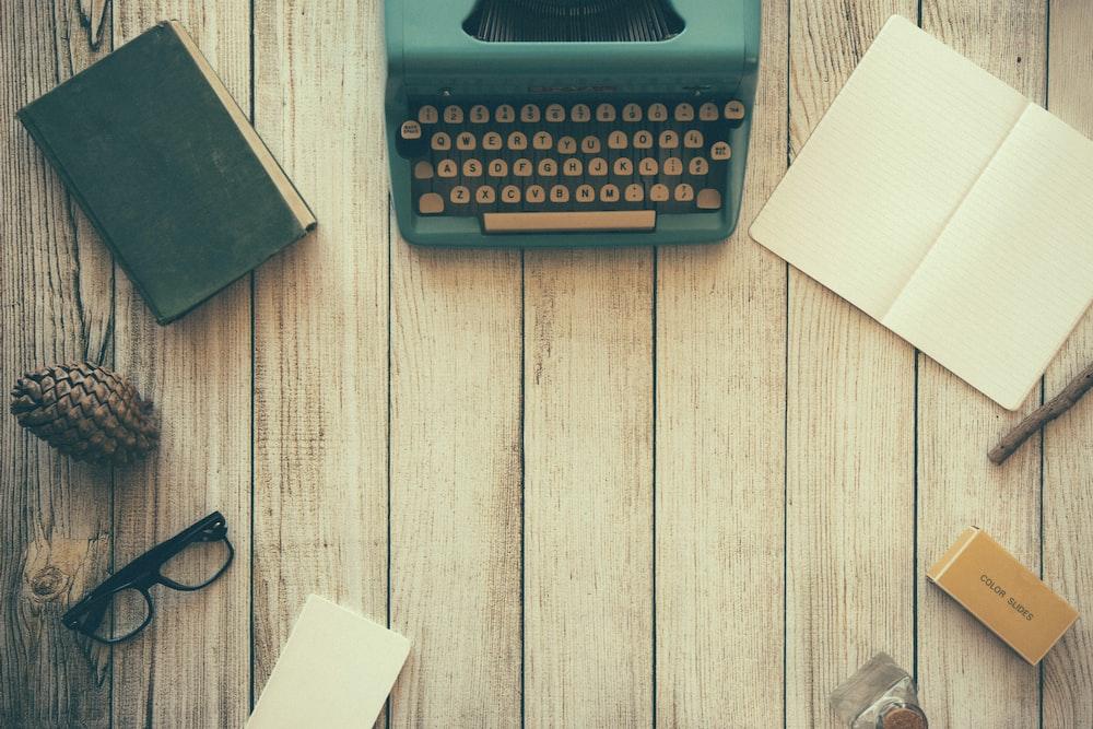 vintage teal typewriter beside book