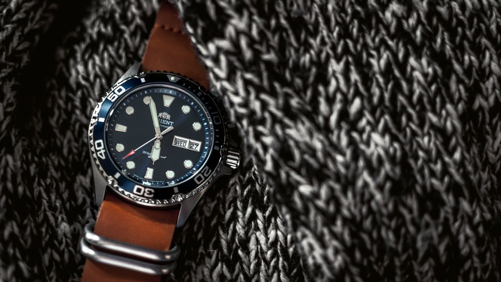 round black analog watch with brown leather strap on black and white knitted textile