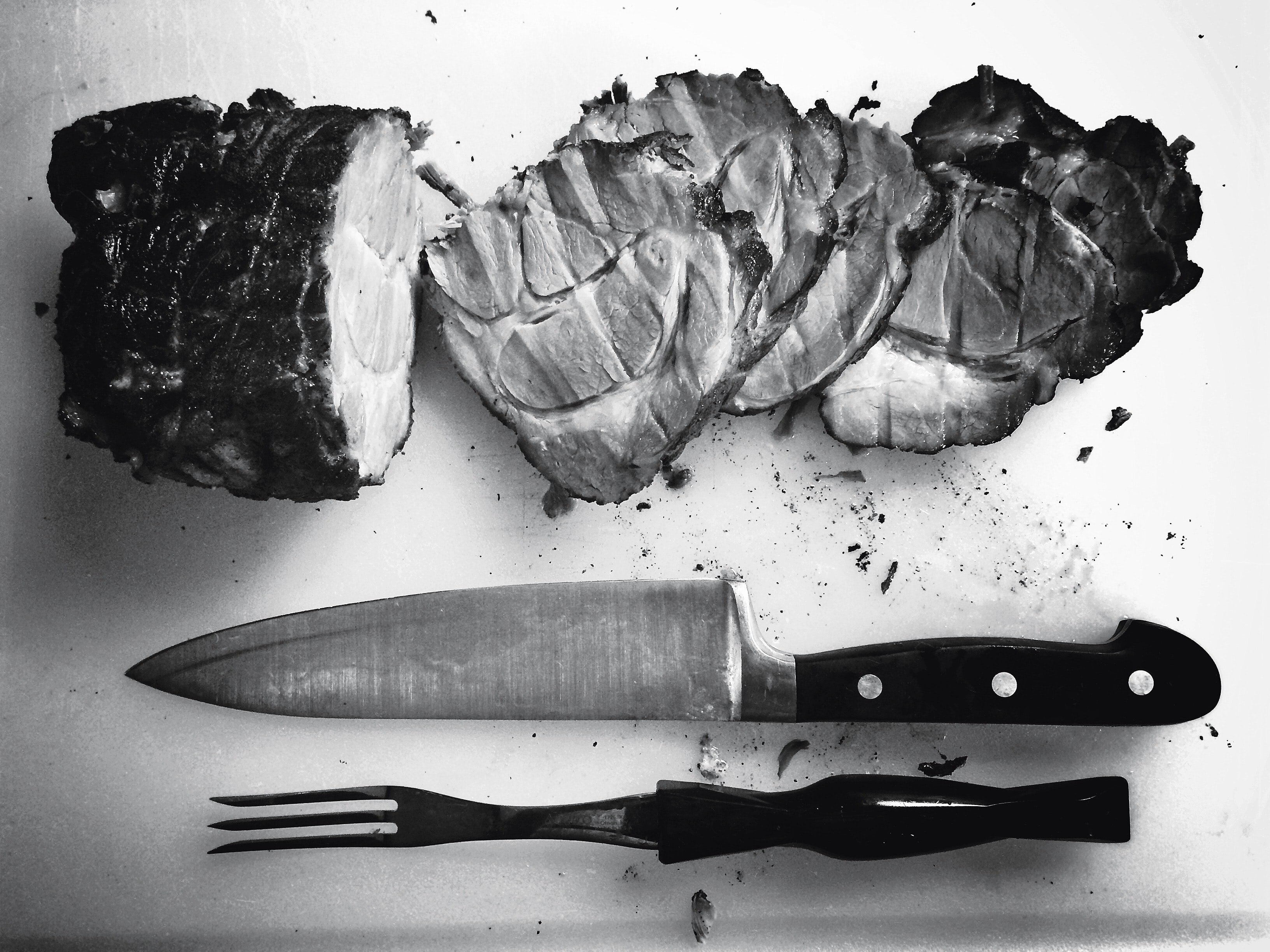 A black-and-white shot of a knife and fork next to a cut ham