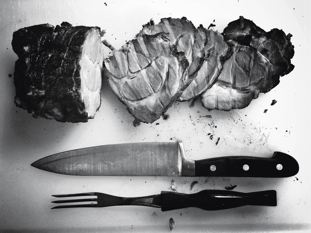 grayscale photo of grilled meat beside knife and fork