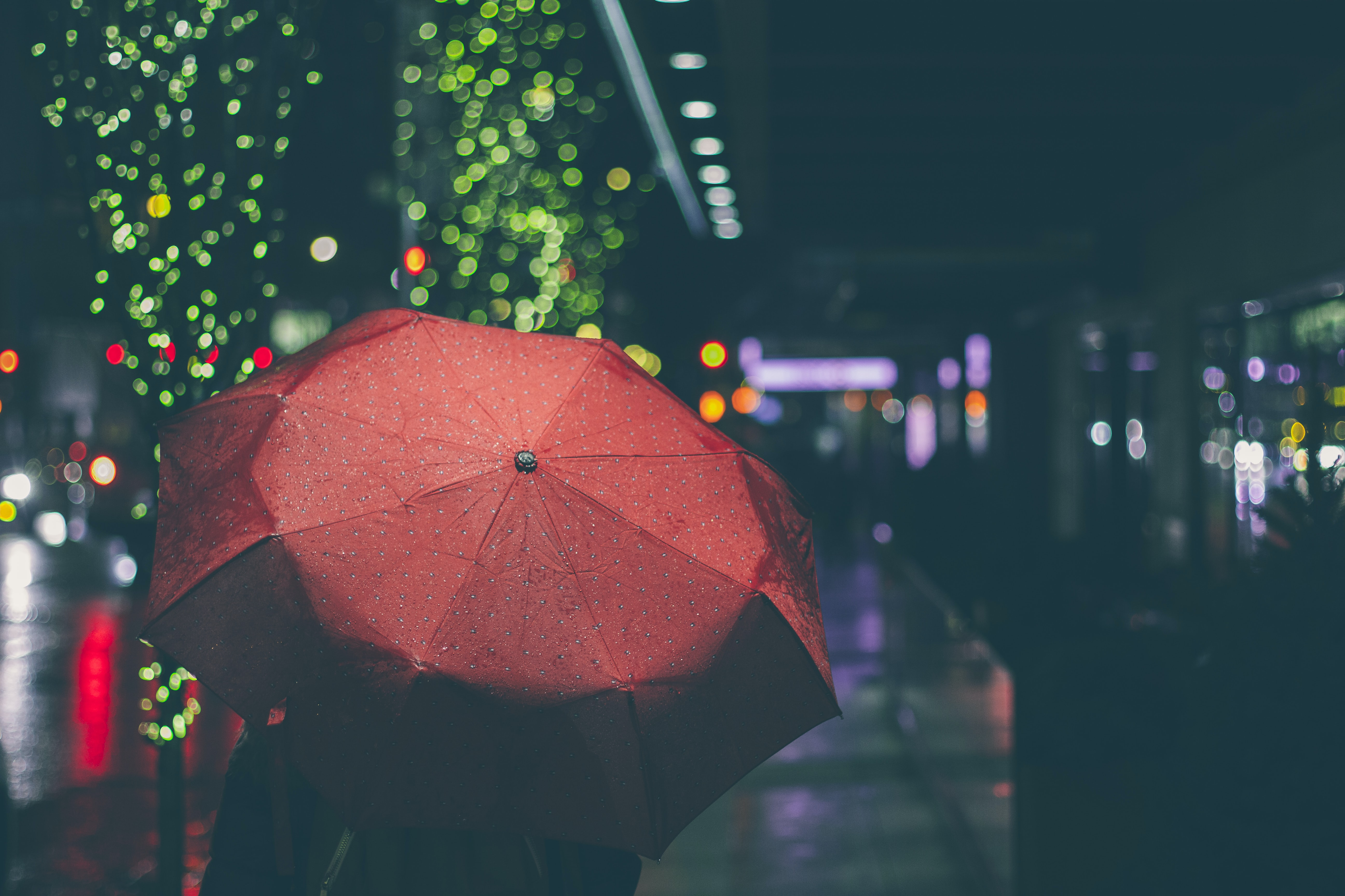 Person carries a red umbrella on a rainy night in the city