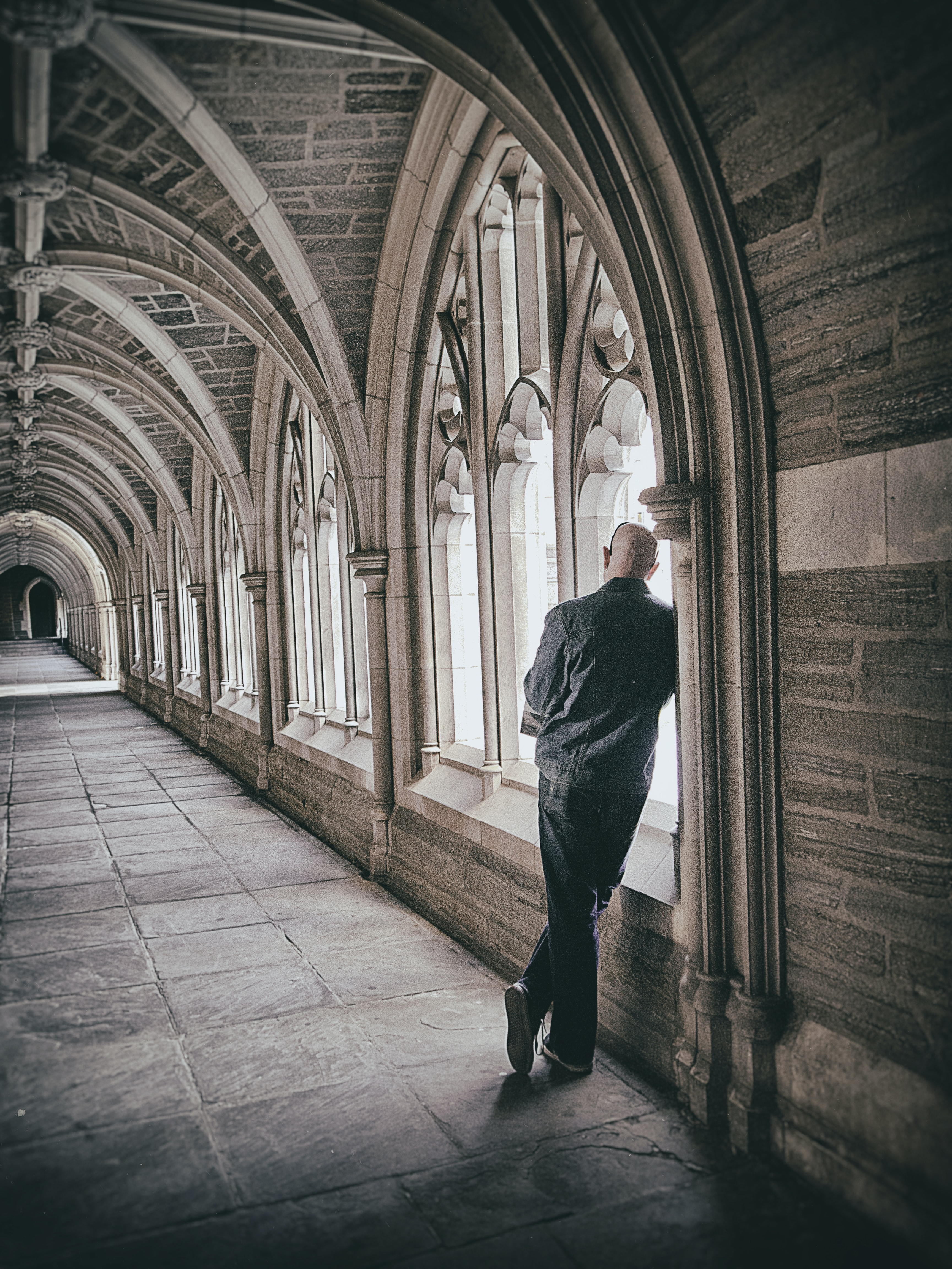 Man leaning against wall in gothic, medieval hallway architecture near windows with light coming through