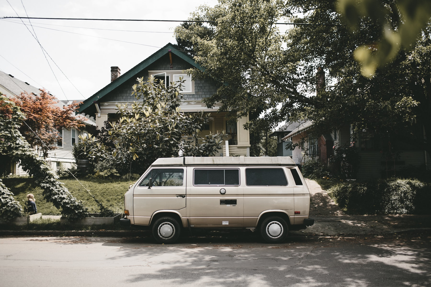 Volkswagen camper van parked on the side of the street in front of a house