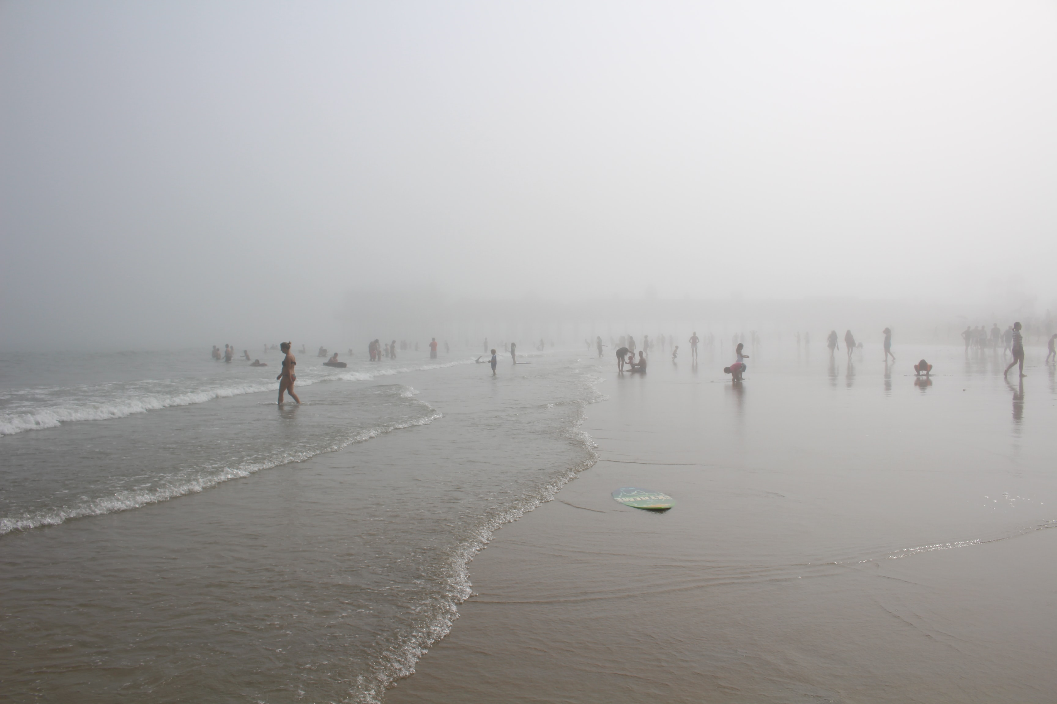 People relishing the fog at mist covered beach