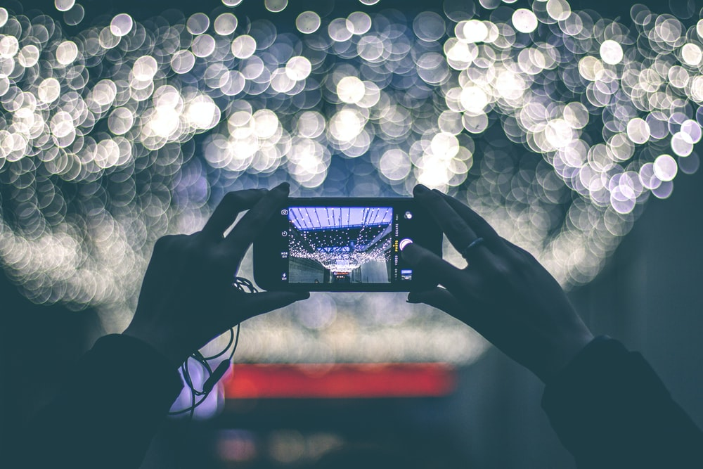 selective focus photography of person holding smartphone while taking picture of scenery