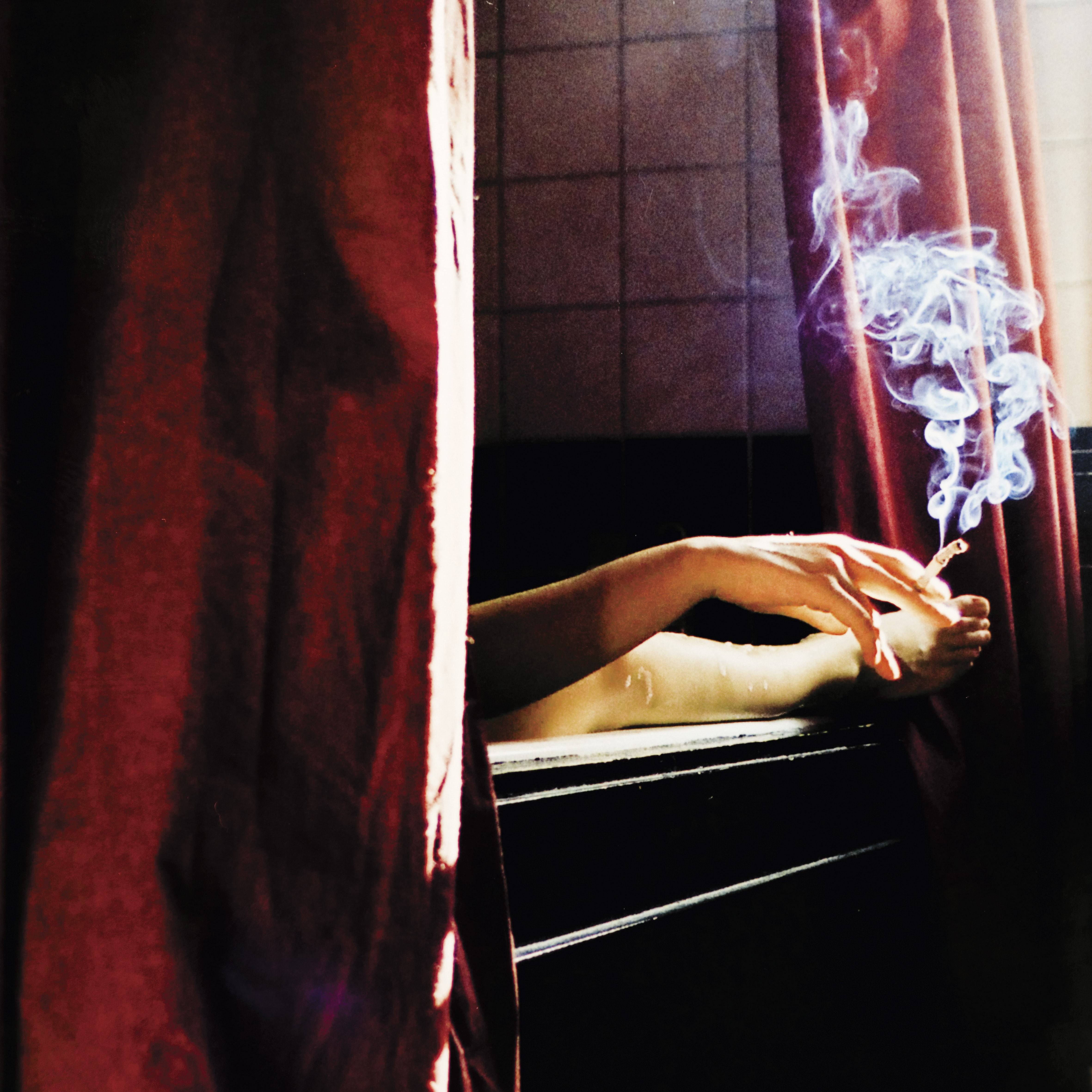A woman in a bathtub with a cigarette in her hand.