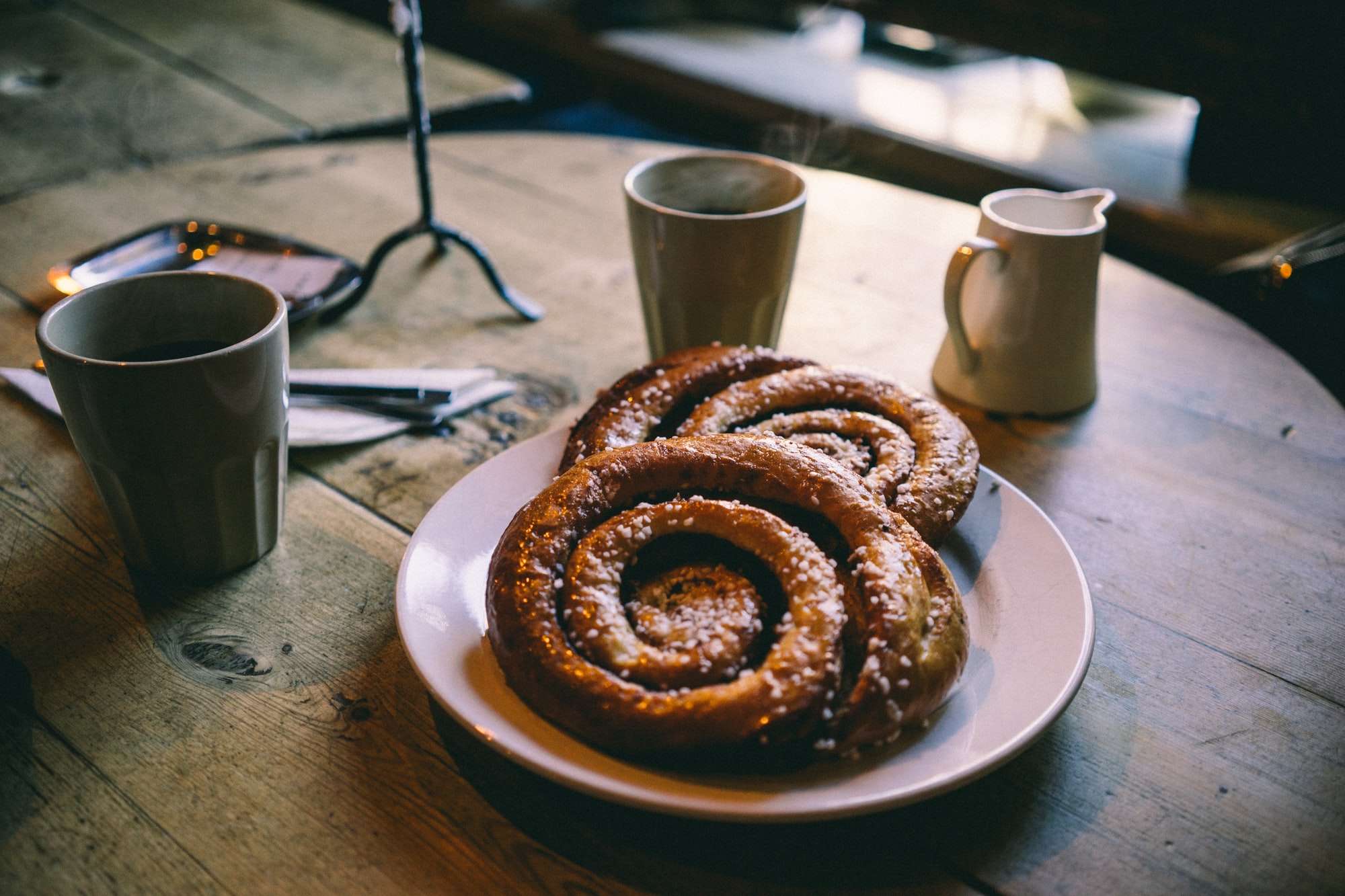 Two large pastries on a white plate with two coffee mugs and cream on a round wooden table