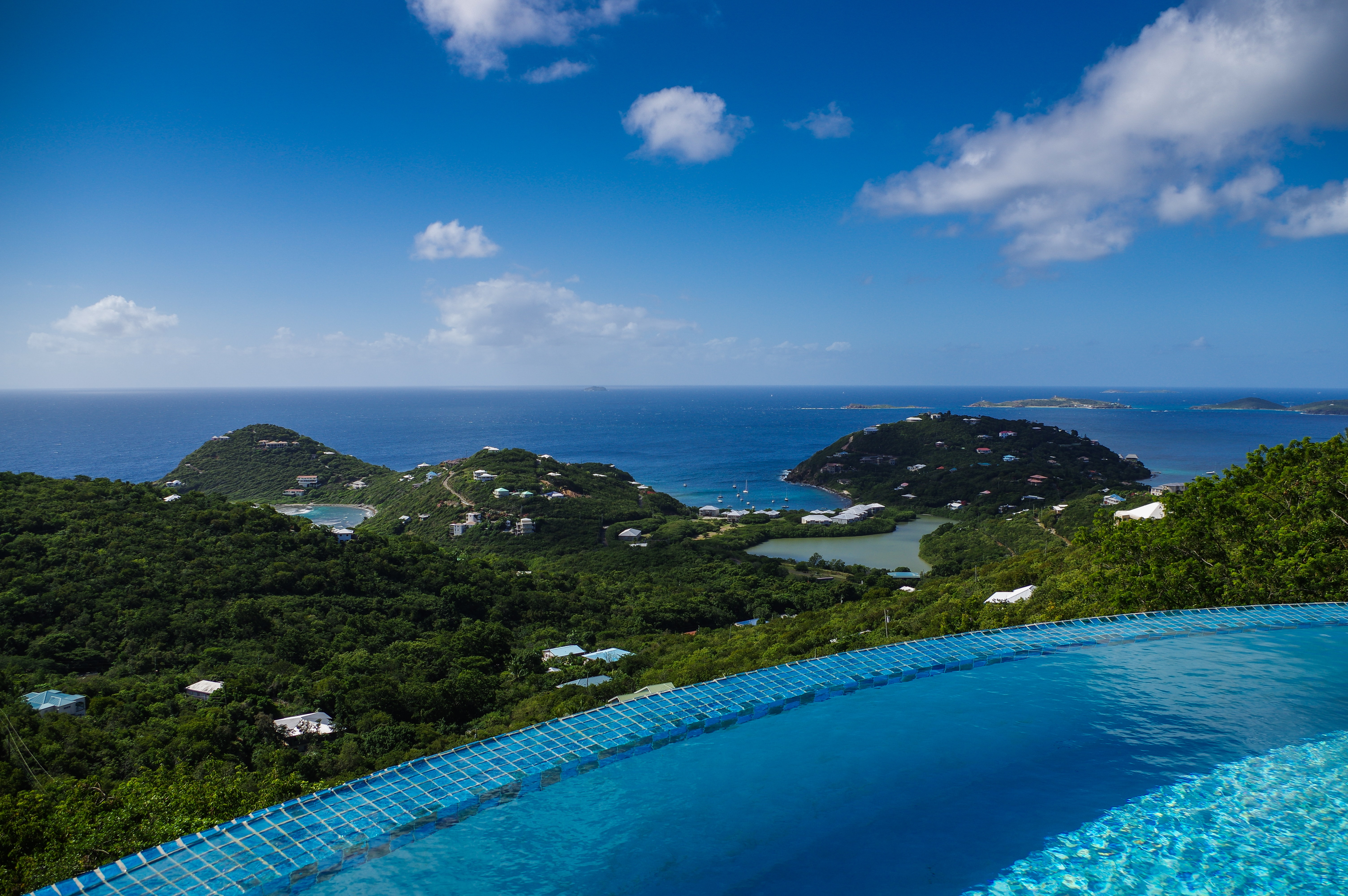 A round infinity pool on a green coast on a bright day