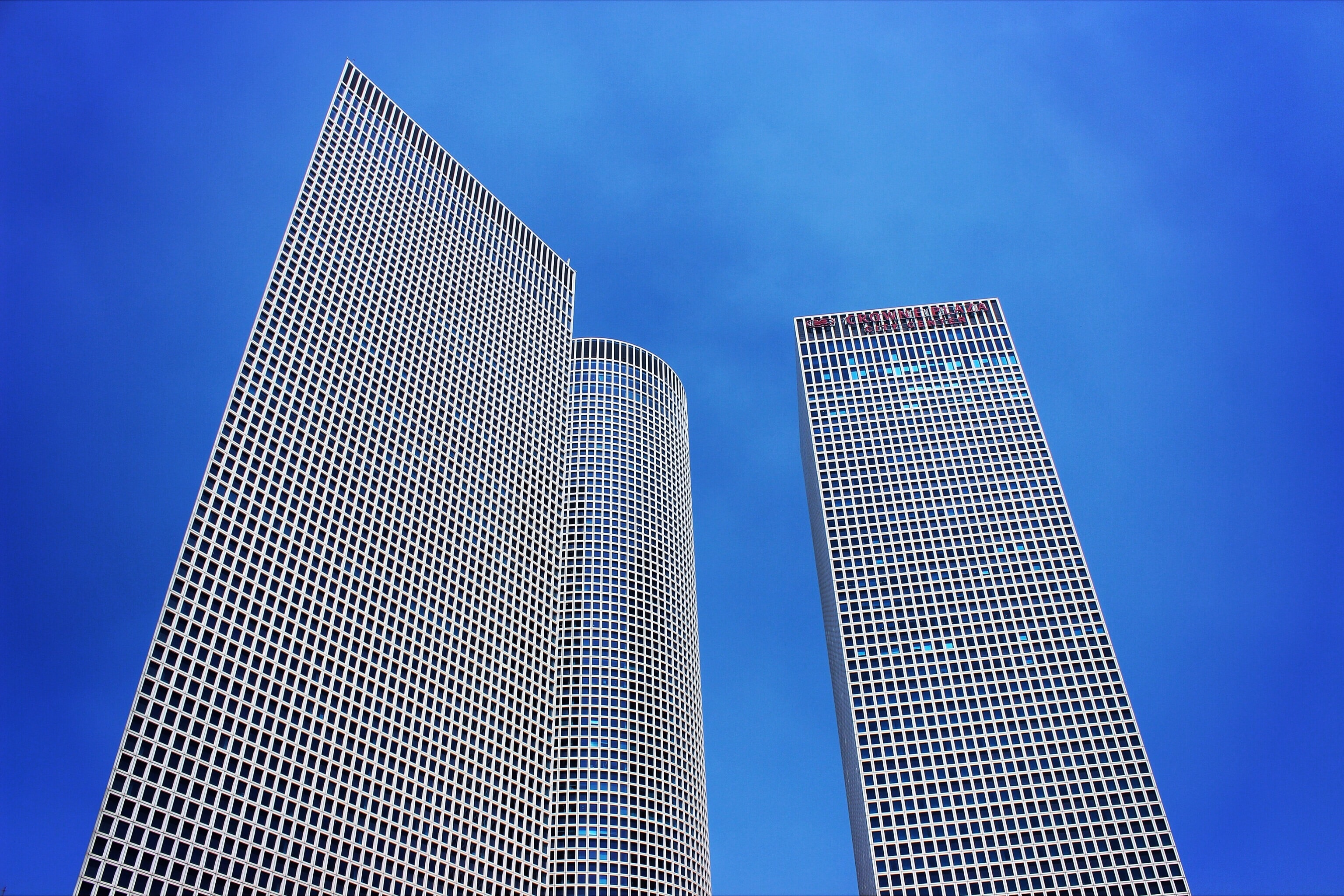 Shot of skyscraper towers with windows from below with clear blue sky