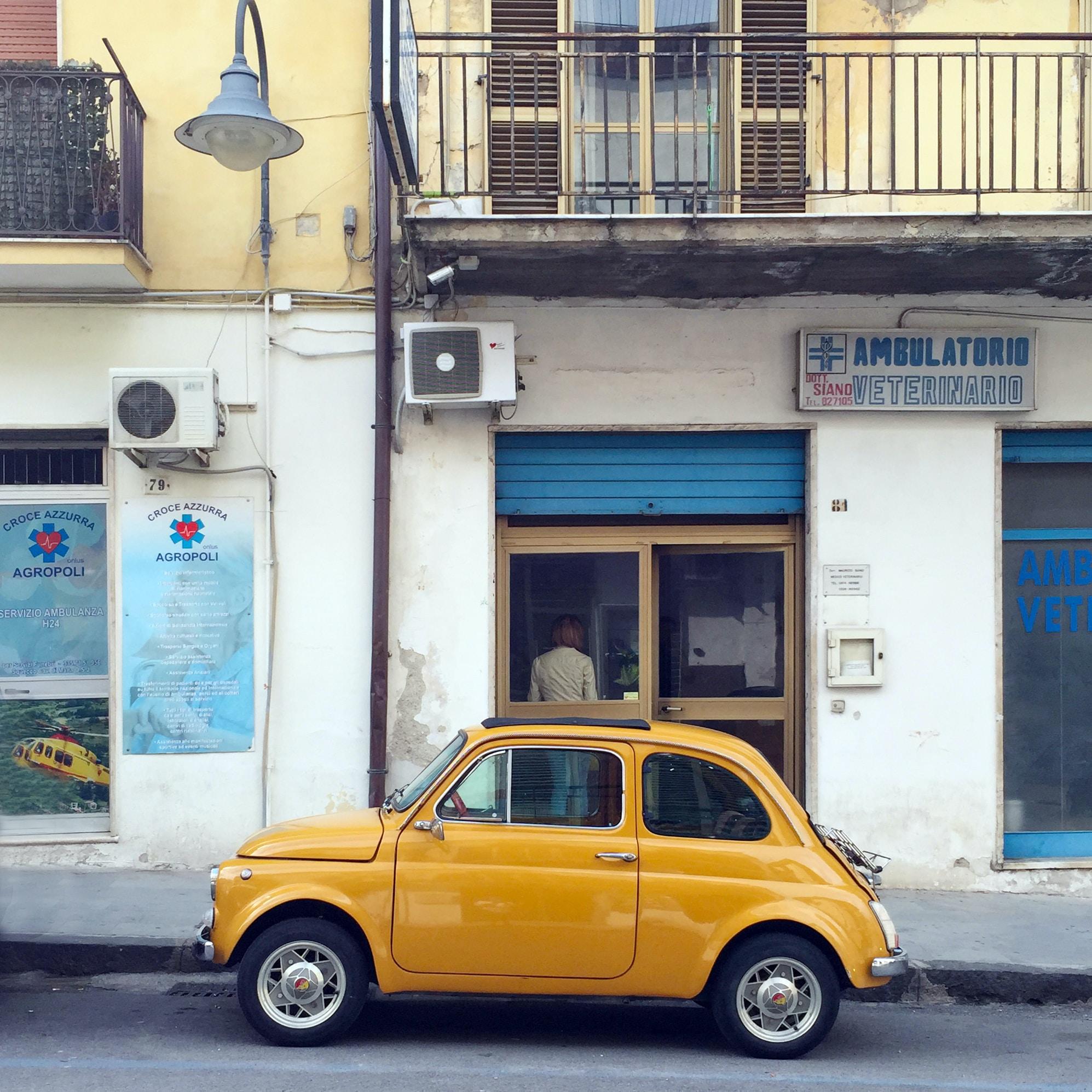 yellow Volkswagen Beetle in front of concrete building