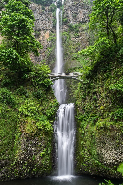gray concrete bridge and waterfalls during daytime