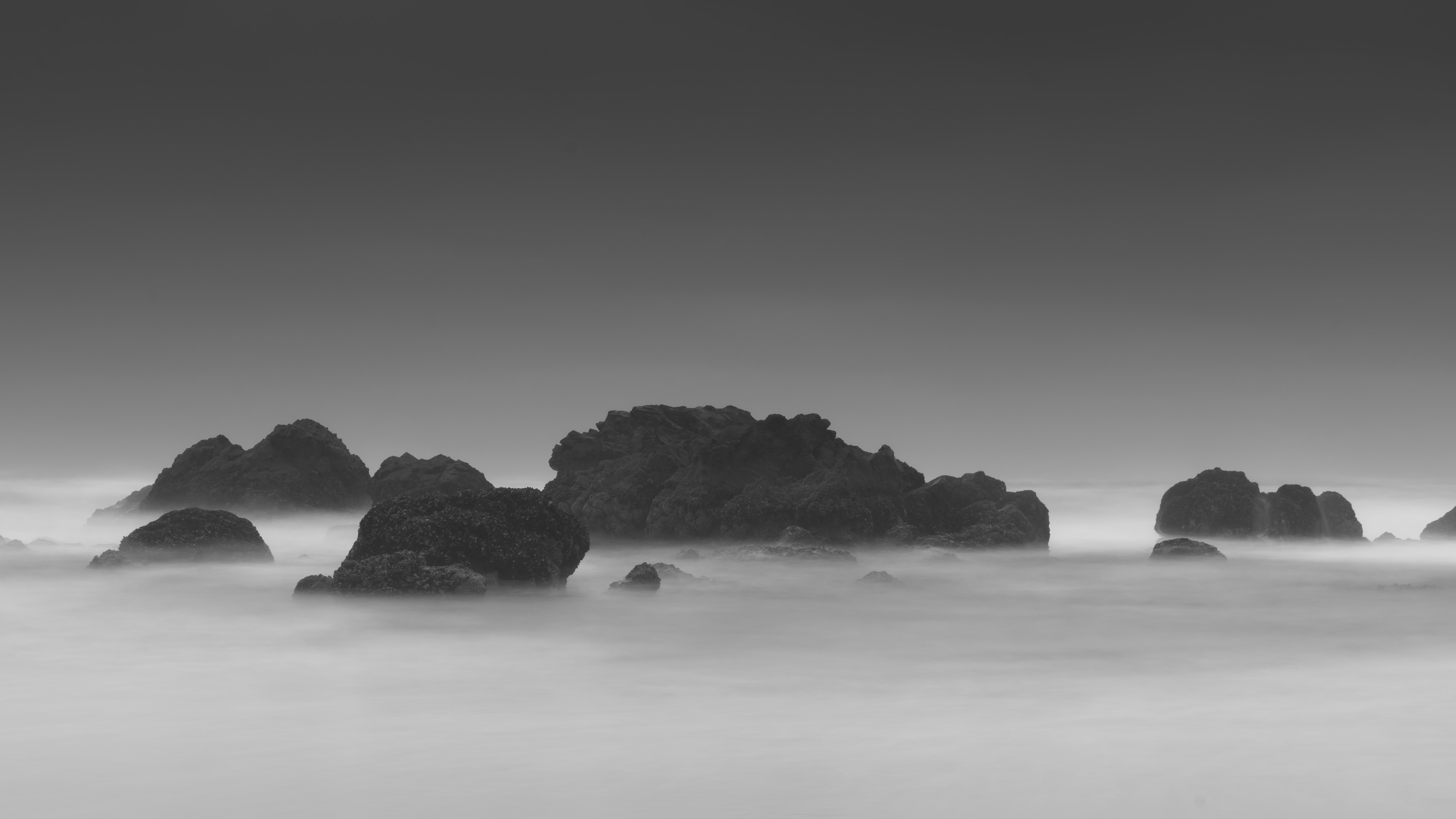A black-and-white shot of large rocks jutting out from the frothy sea