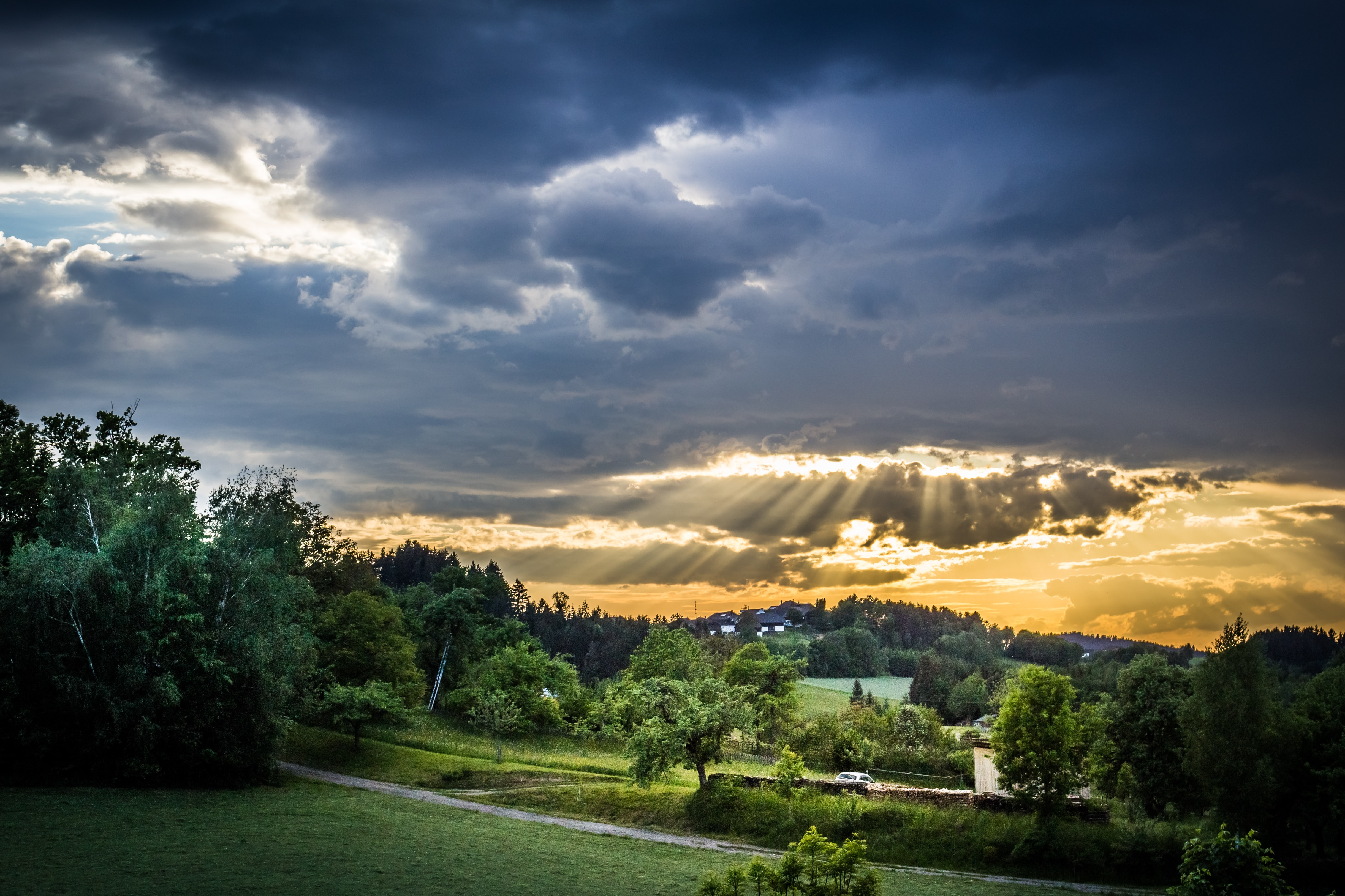 Sunbeams shine from storm clouds over a lush green farm field