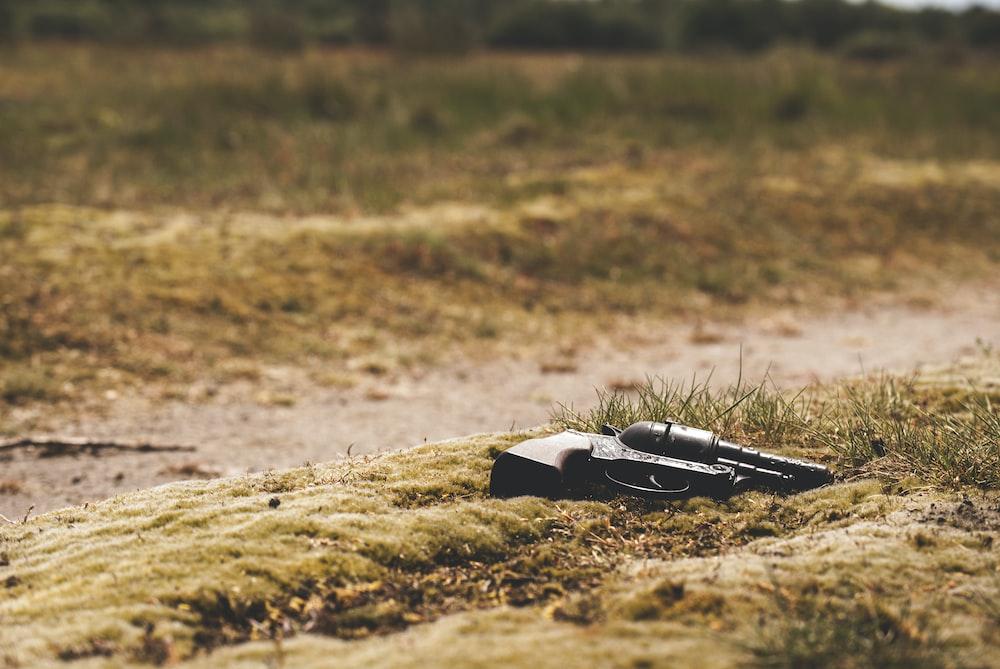 black revolver pistol on ground during daytime