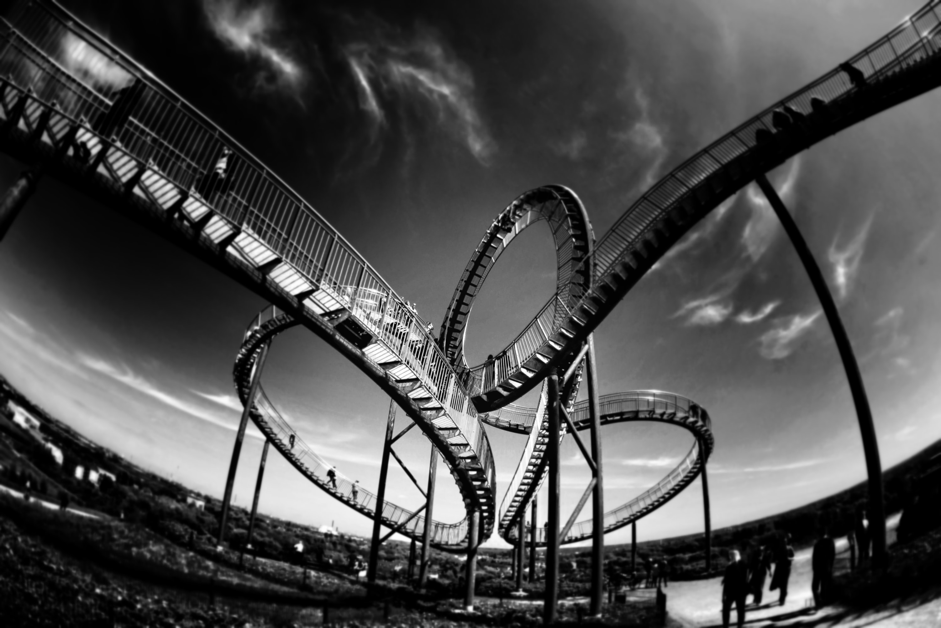 Black and white shot of winding roller coaster at amusement theme park