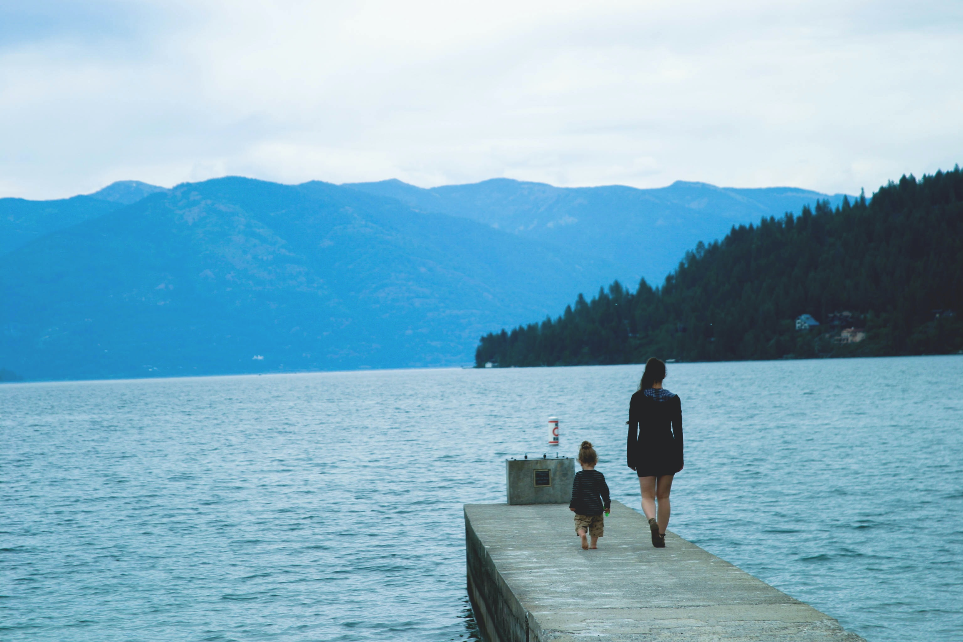 A woman and a child walking down a wooden dock towards a forest lake