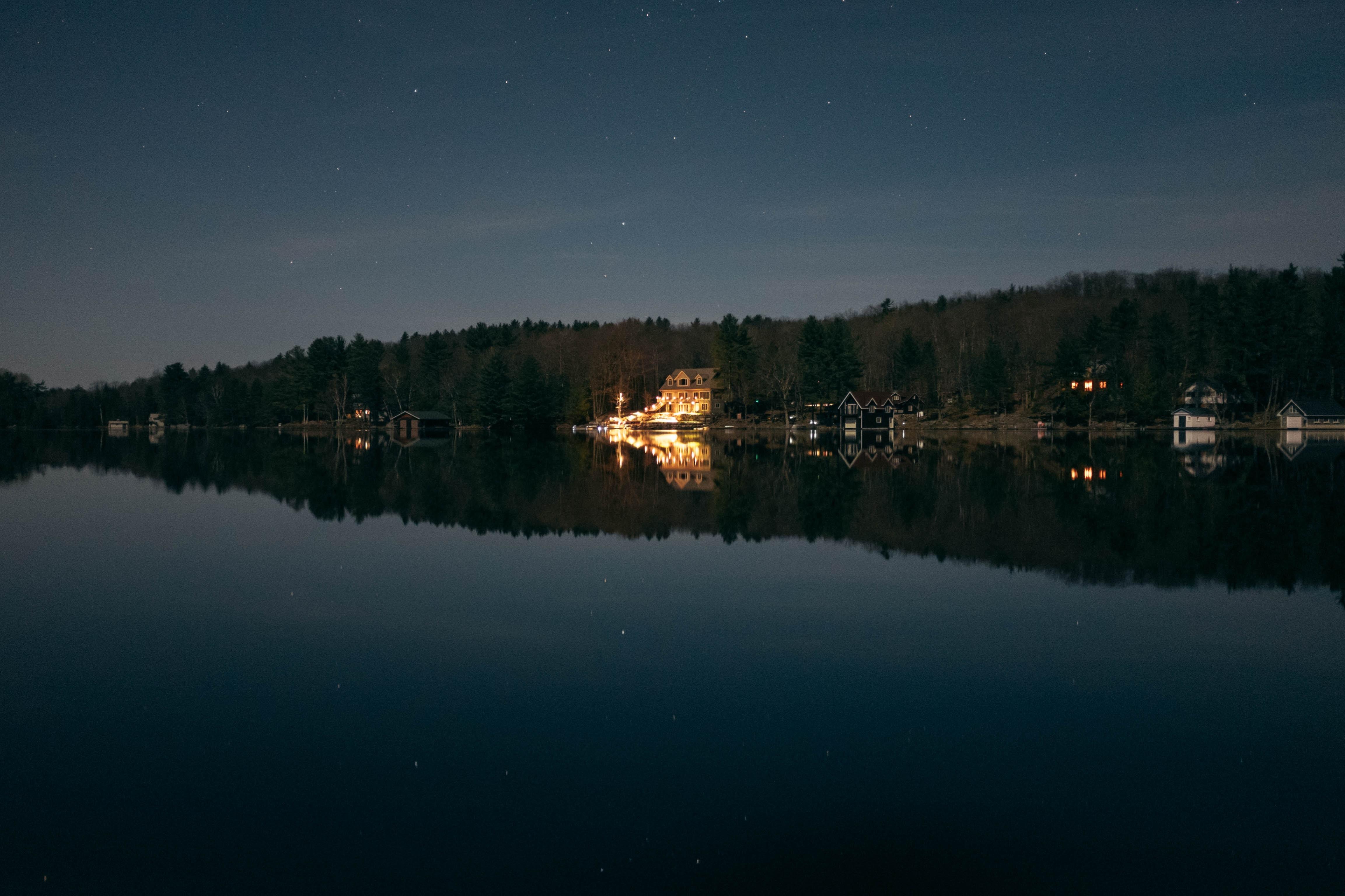 lighted beige house beside shoreline during nighttime