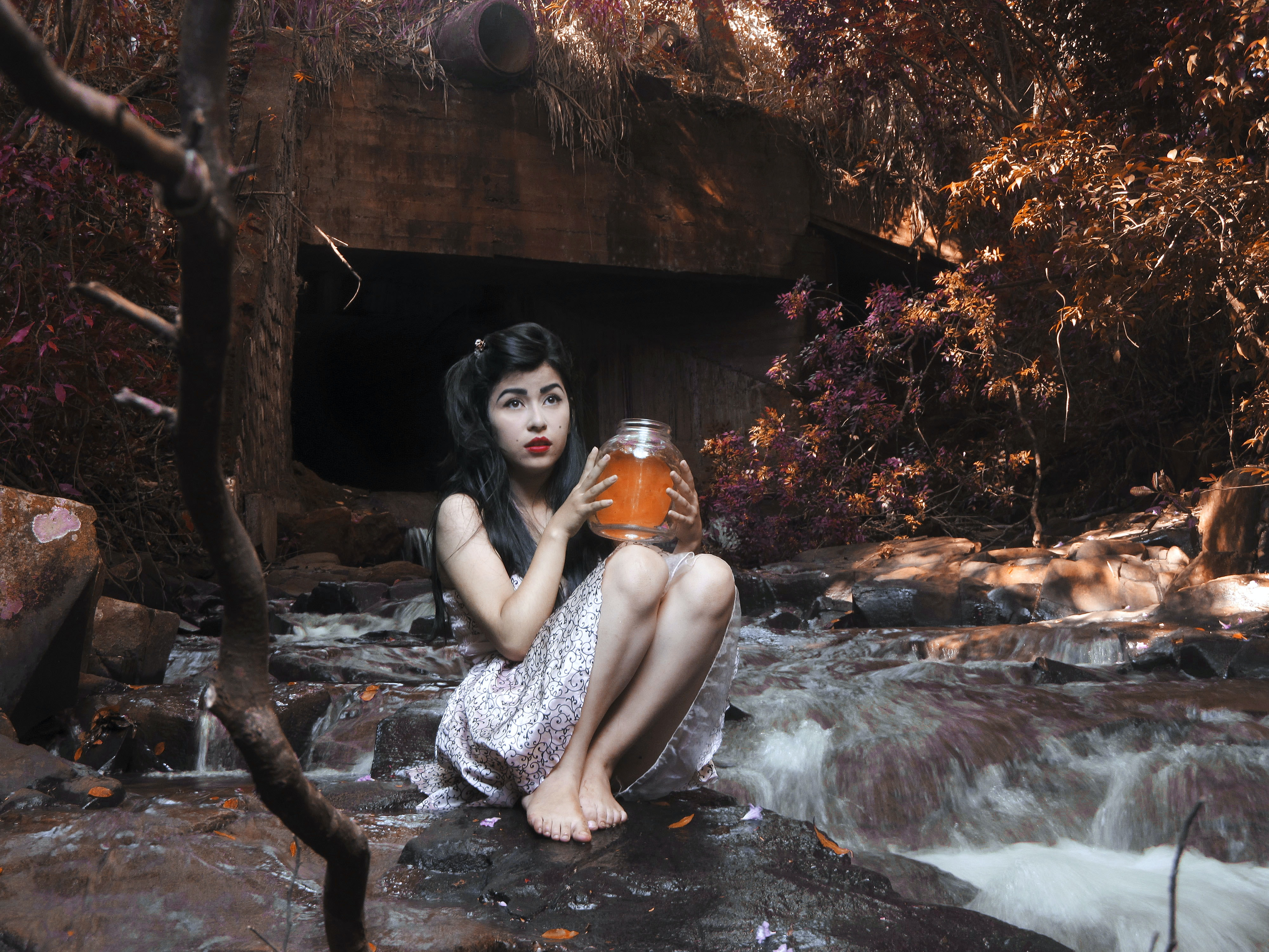 woman carrying glass jar while sitting on boulder beside flowing river behind brown bridge under shade of tree at daytime
