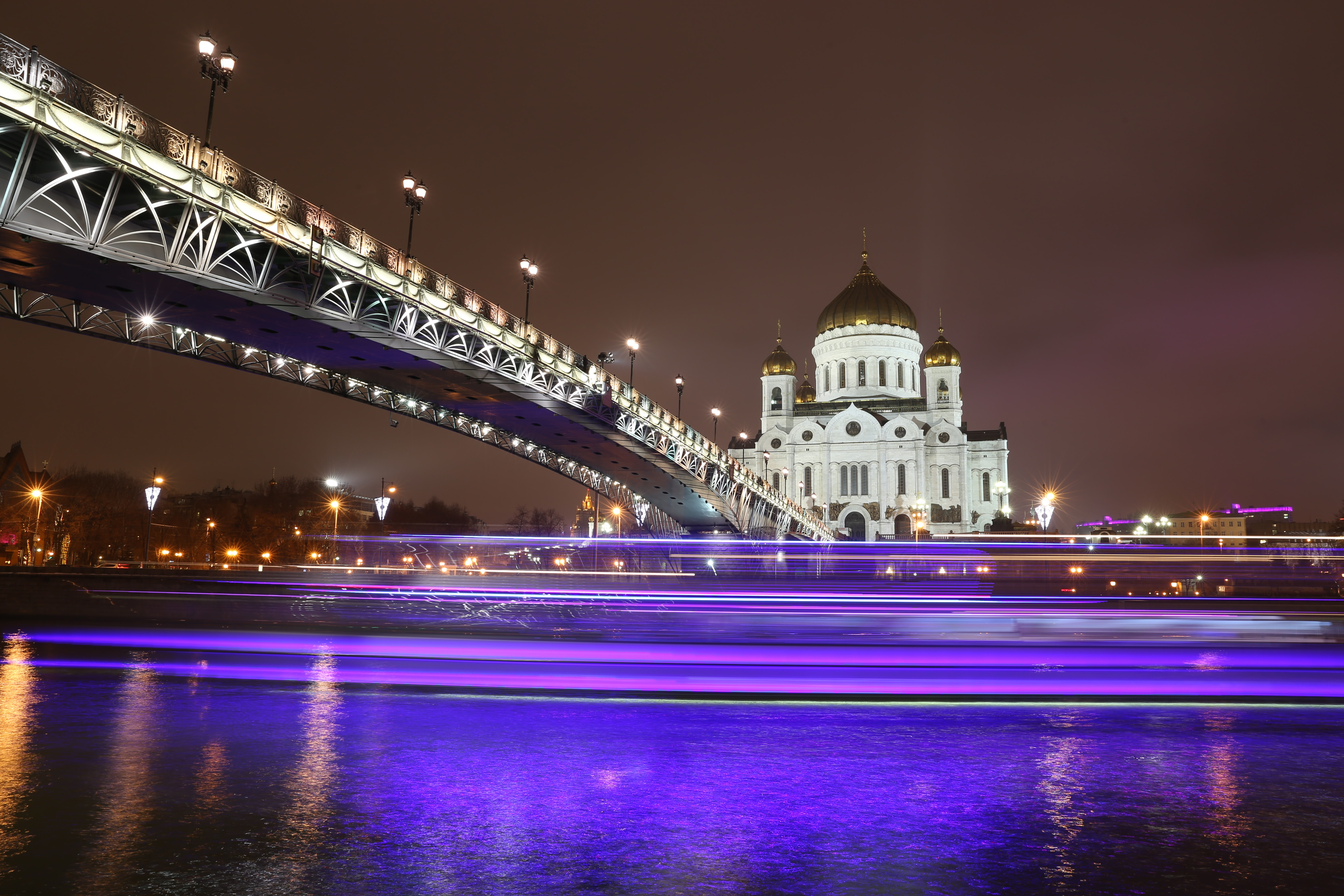 Water glows purple below an ornate bridge and building