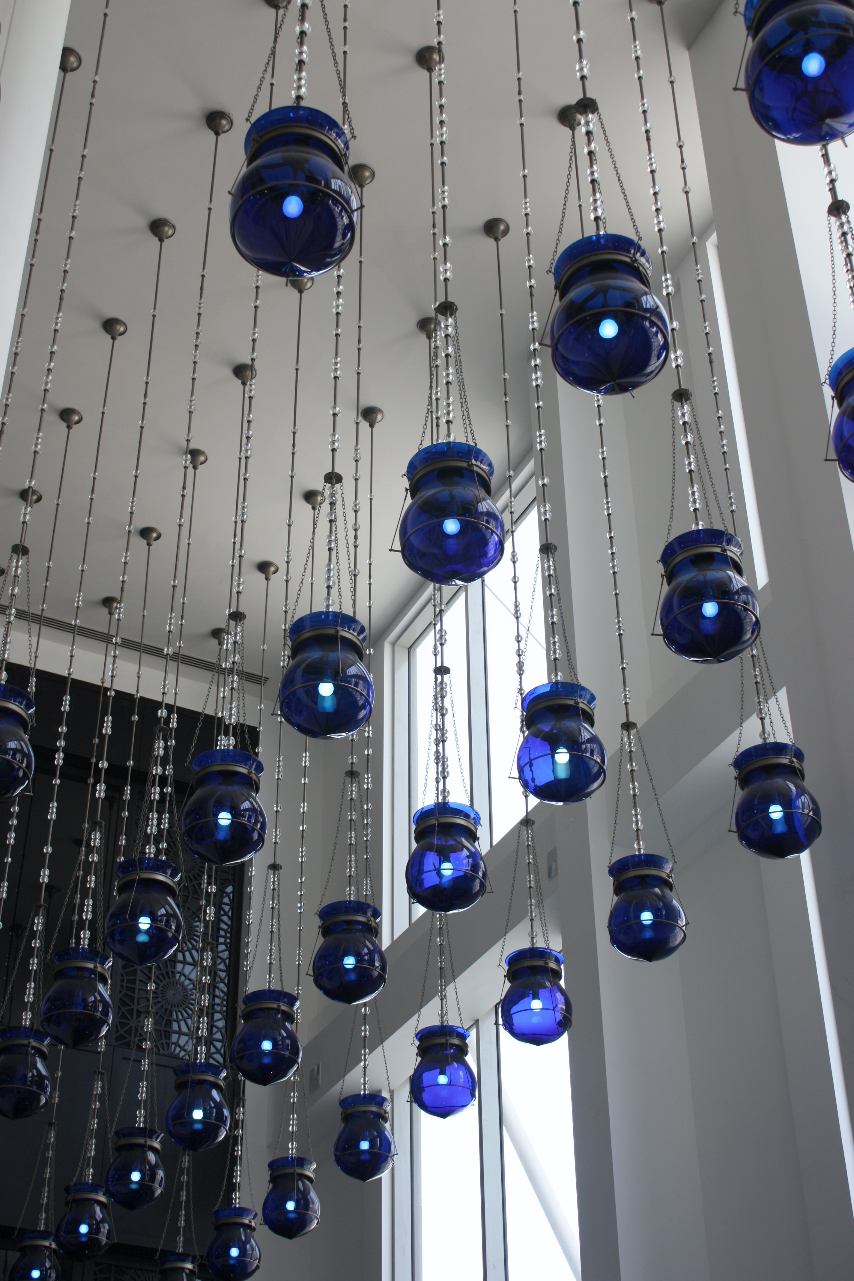 Blue lanterns hanging from the ceiling in a white tall room