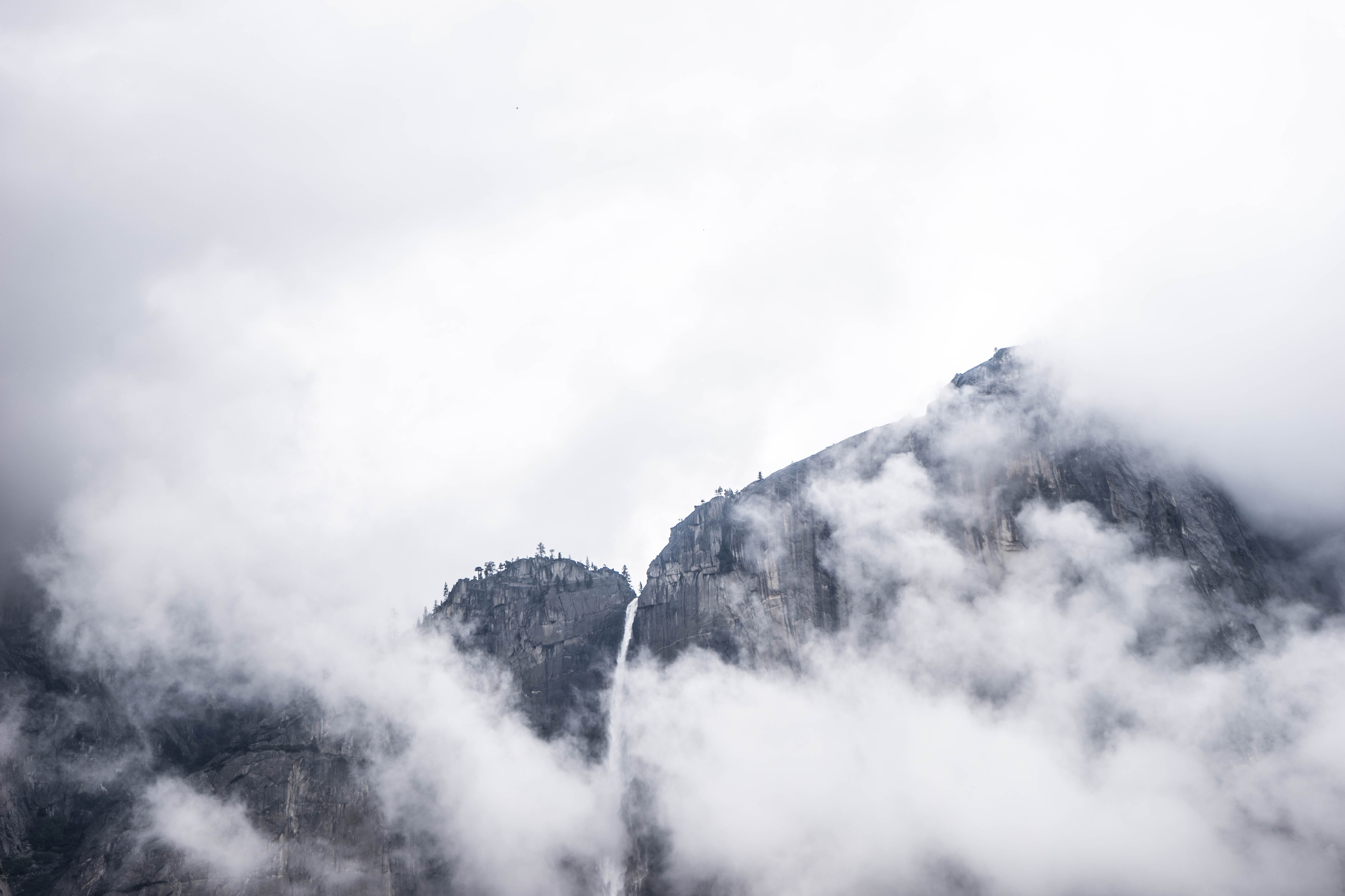 Clouds cover rocky mountain cliffs in the wild