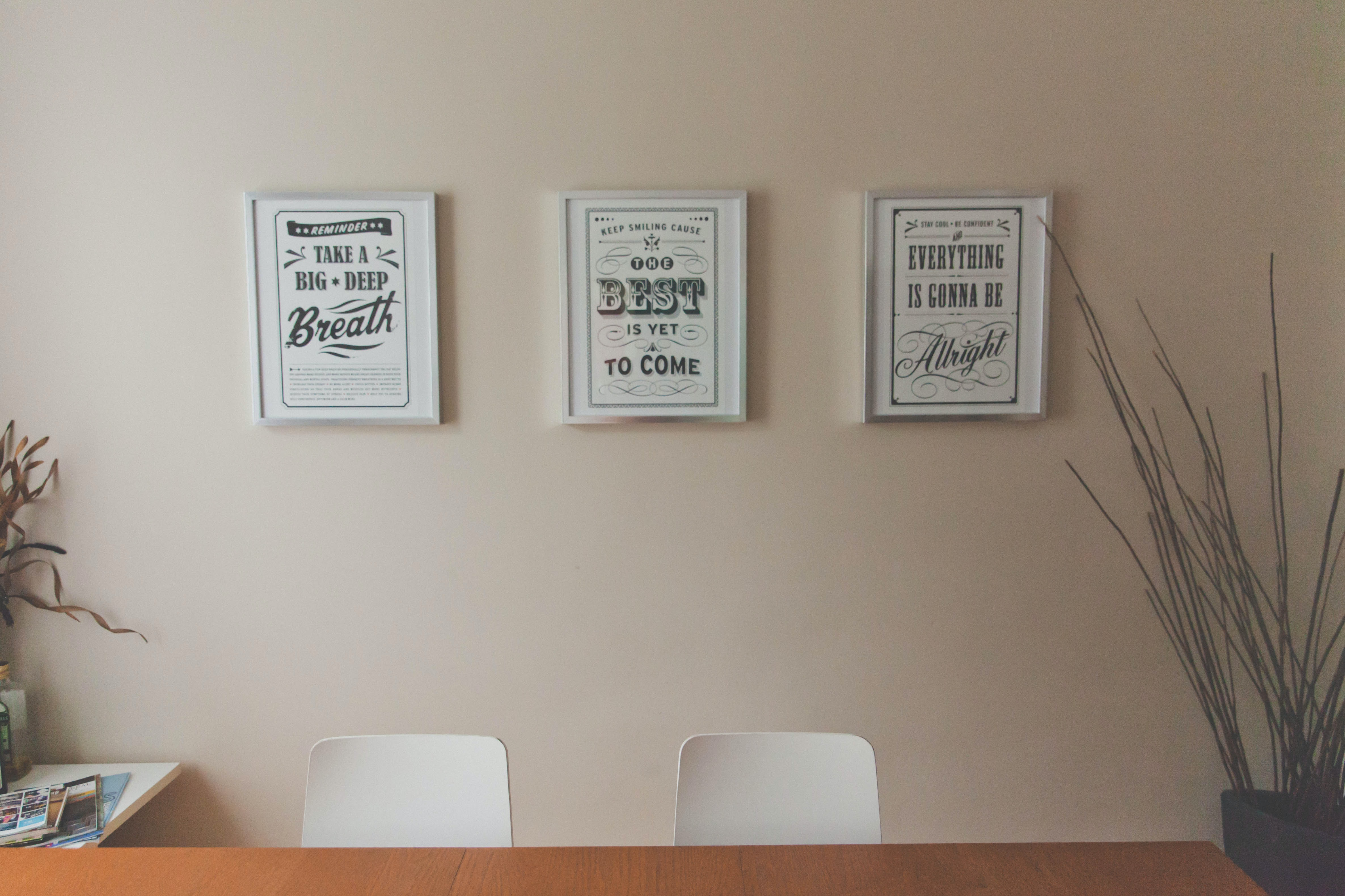Three framed motivational posters on a wall in an office