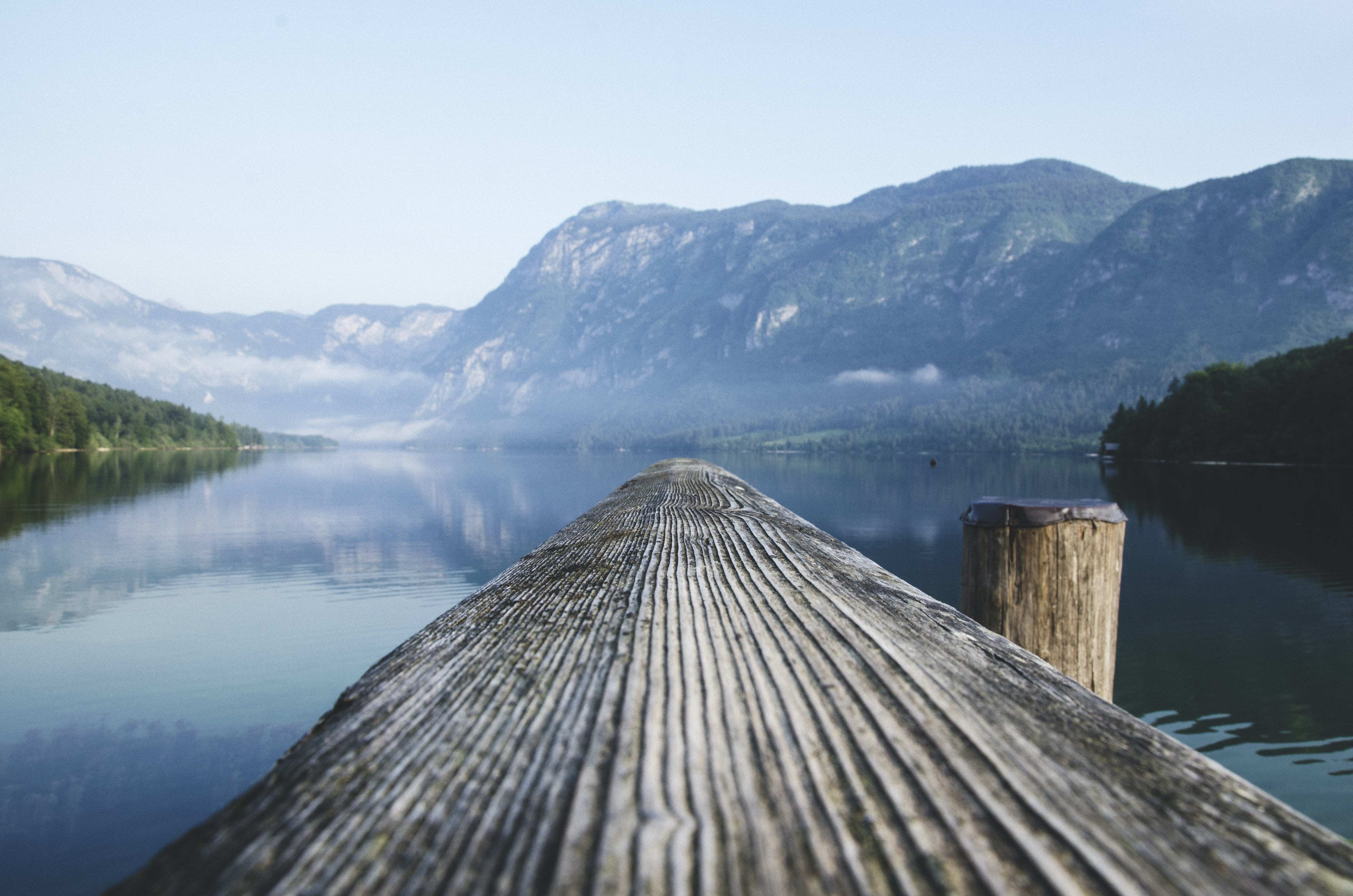 gray wood beam near body of water surrounded by mountain ranges during daytime
