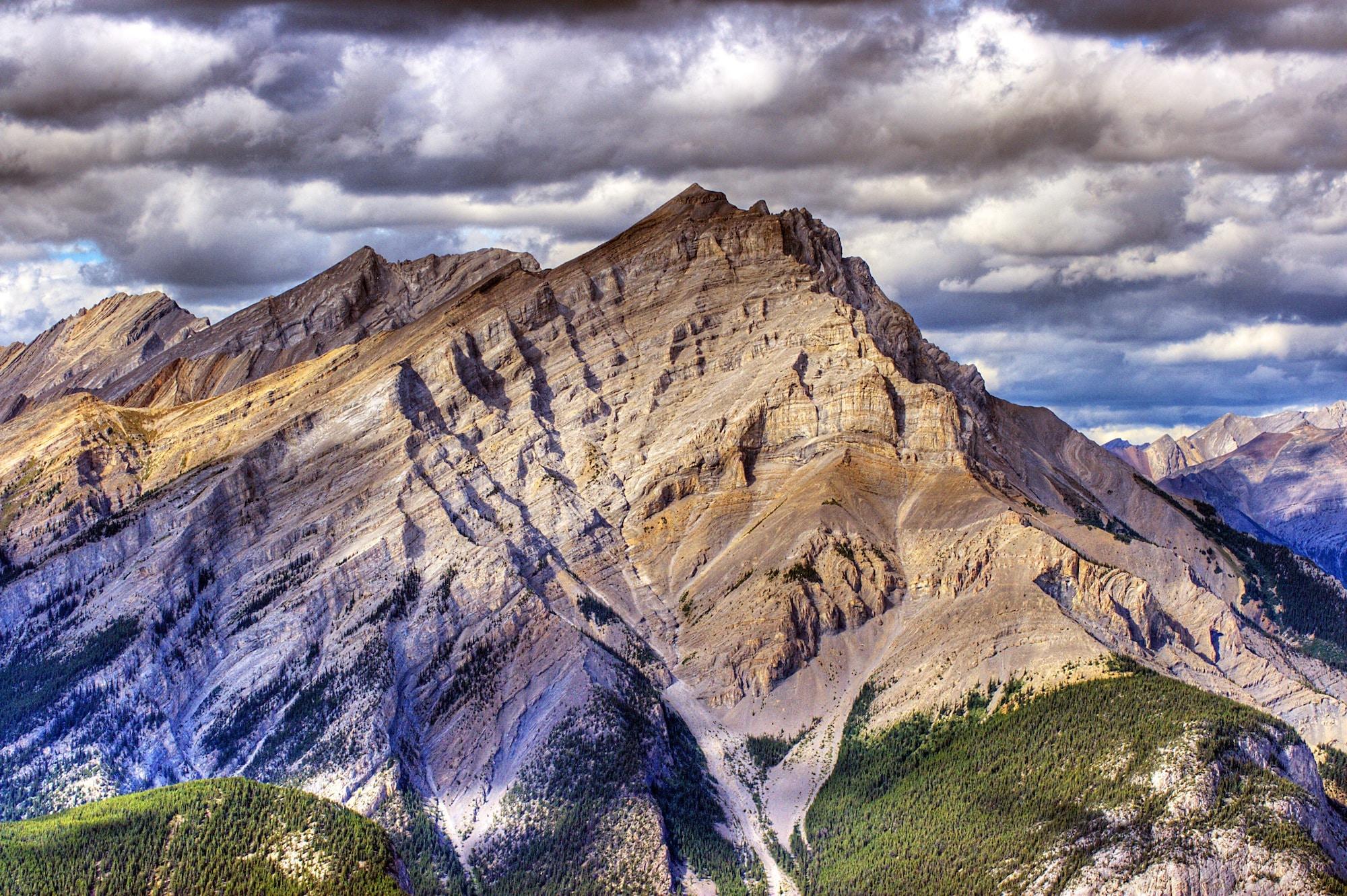 A tall rugged mountain under dense clouds