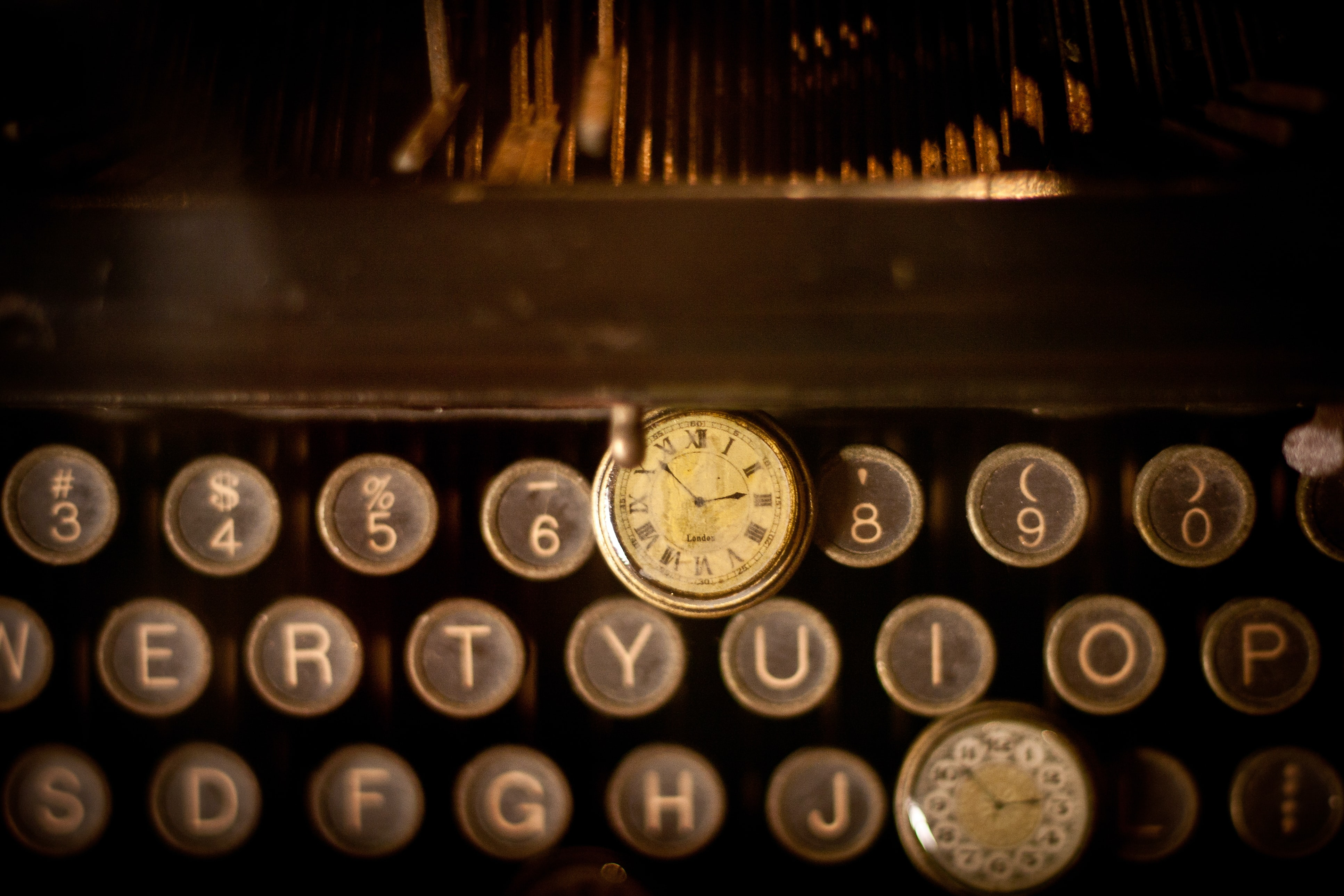 An old pocket watch on a vintage typewriter