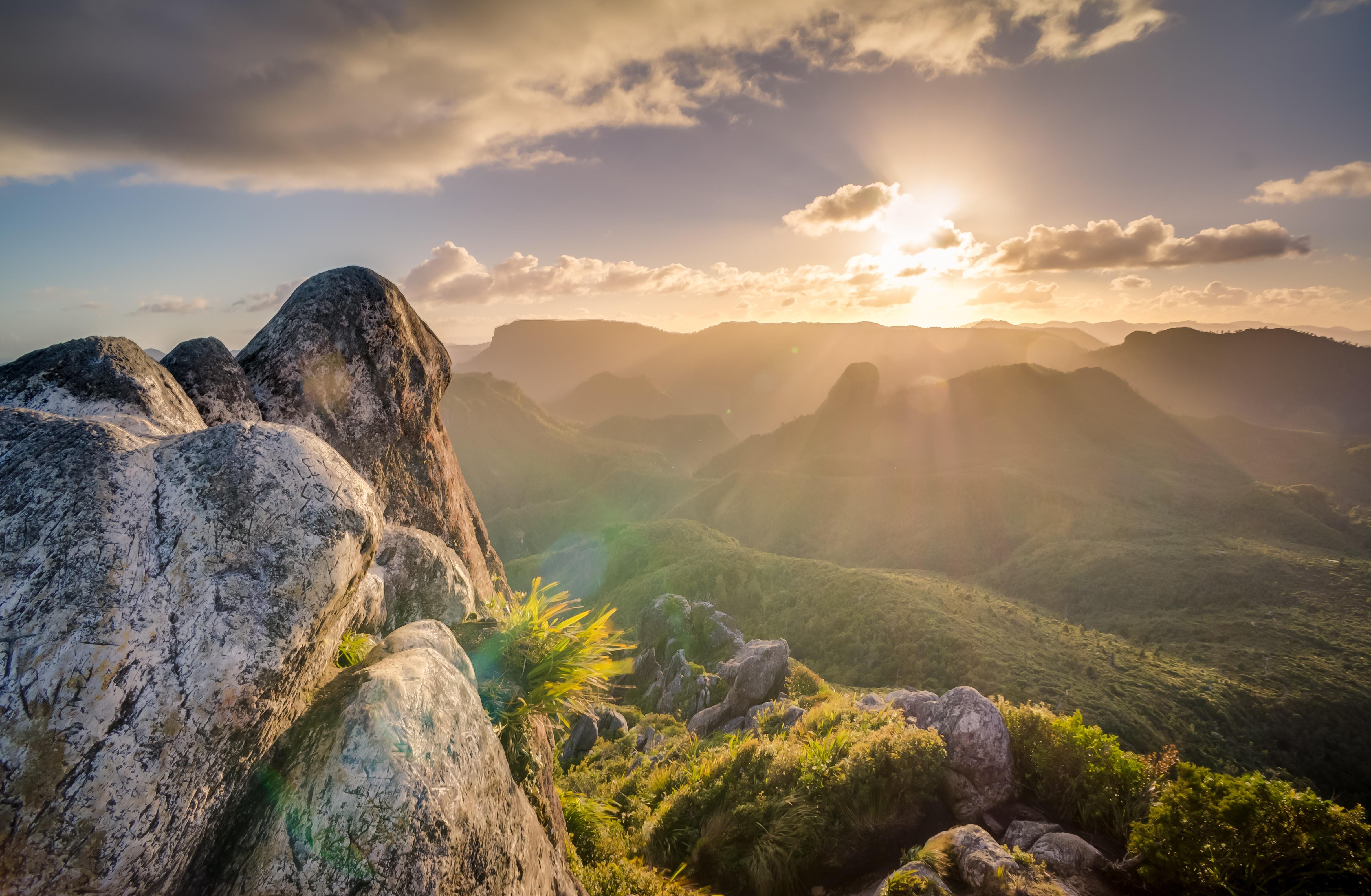 Sun shines over a lush green mountainside