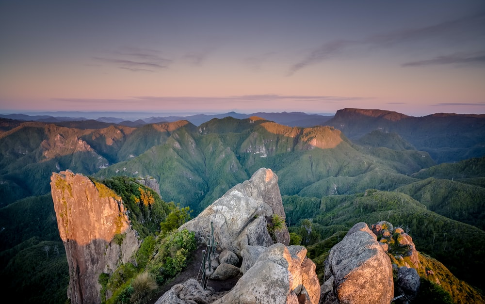 gray stone formation overlooking green hills during golden hour