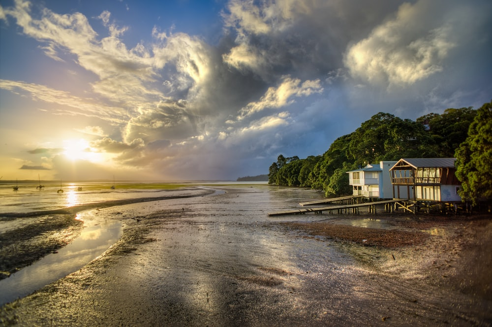 photo of white and brown wooden house beside seashore during sunrise