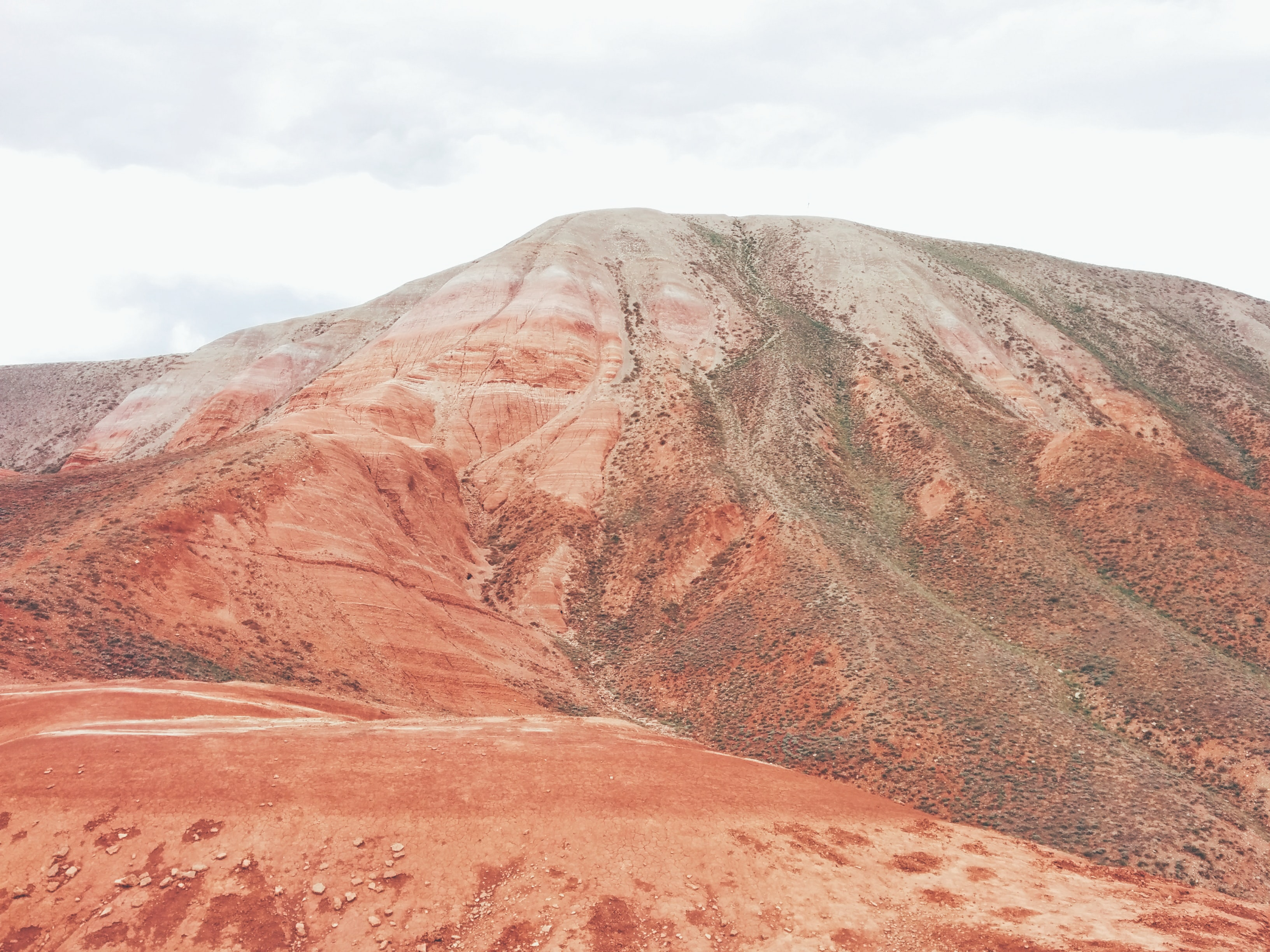 Red sand forms a tall mountain formation in the desert