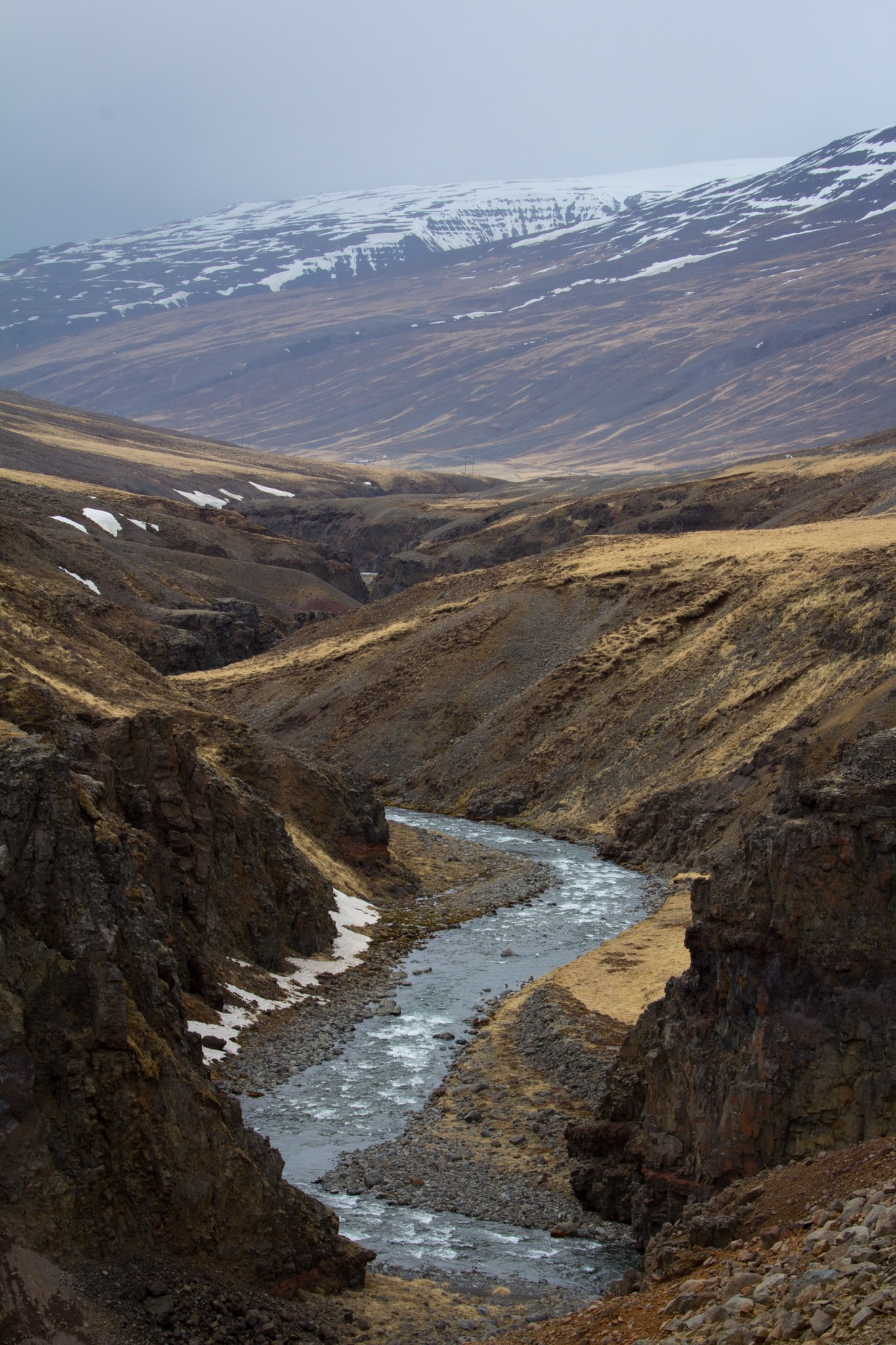 River flowing through a rocky valley with the mountains in the background