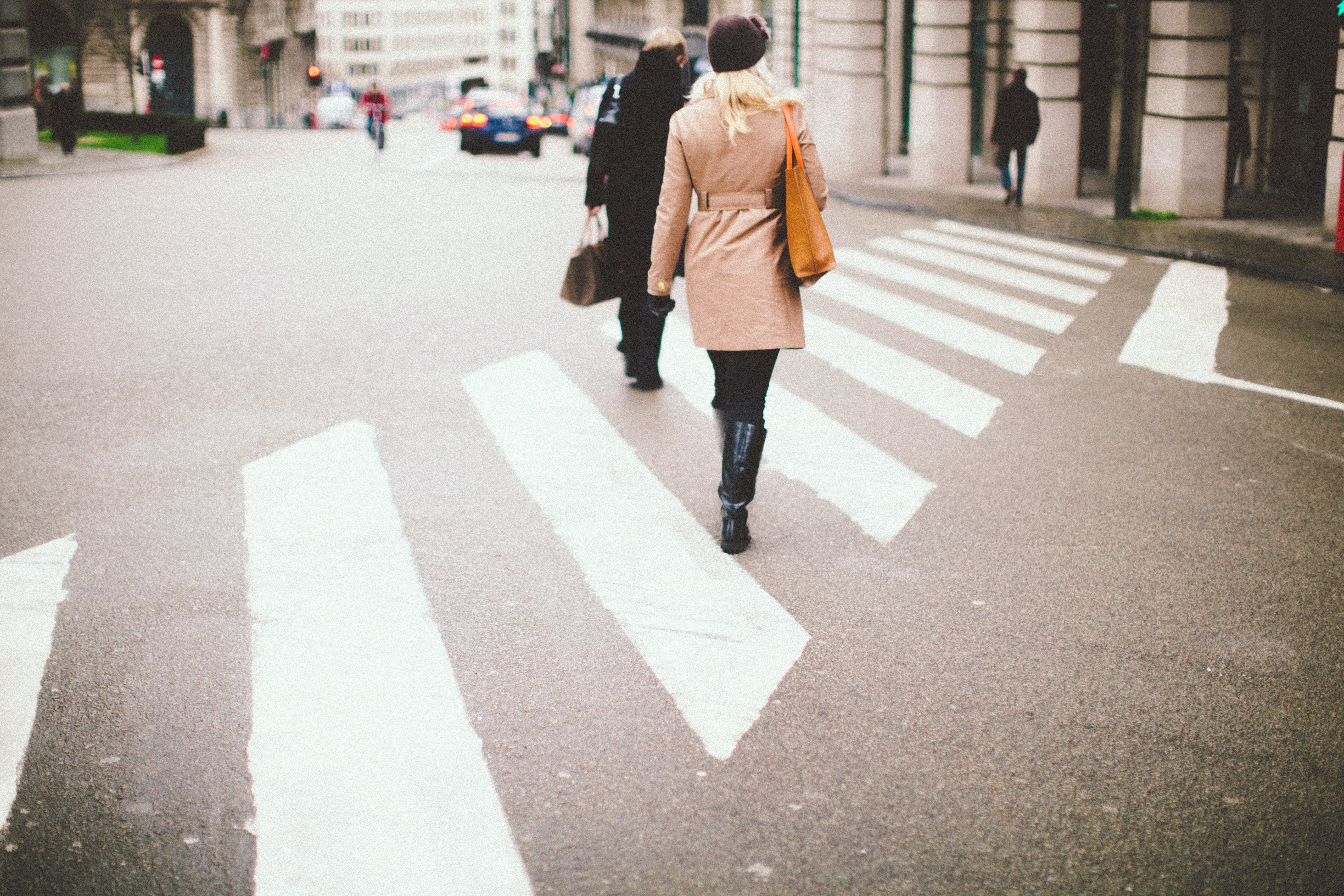 Pedestrians are crossing the road in the crosswalk while the traffic stops in the distance.